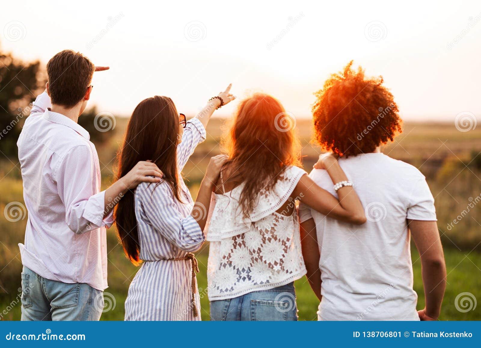 在和两个女孩打扮的两个年轻人时髦的衣裳在领域站立并且在他们前面看在a