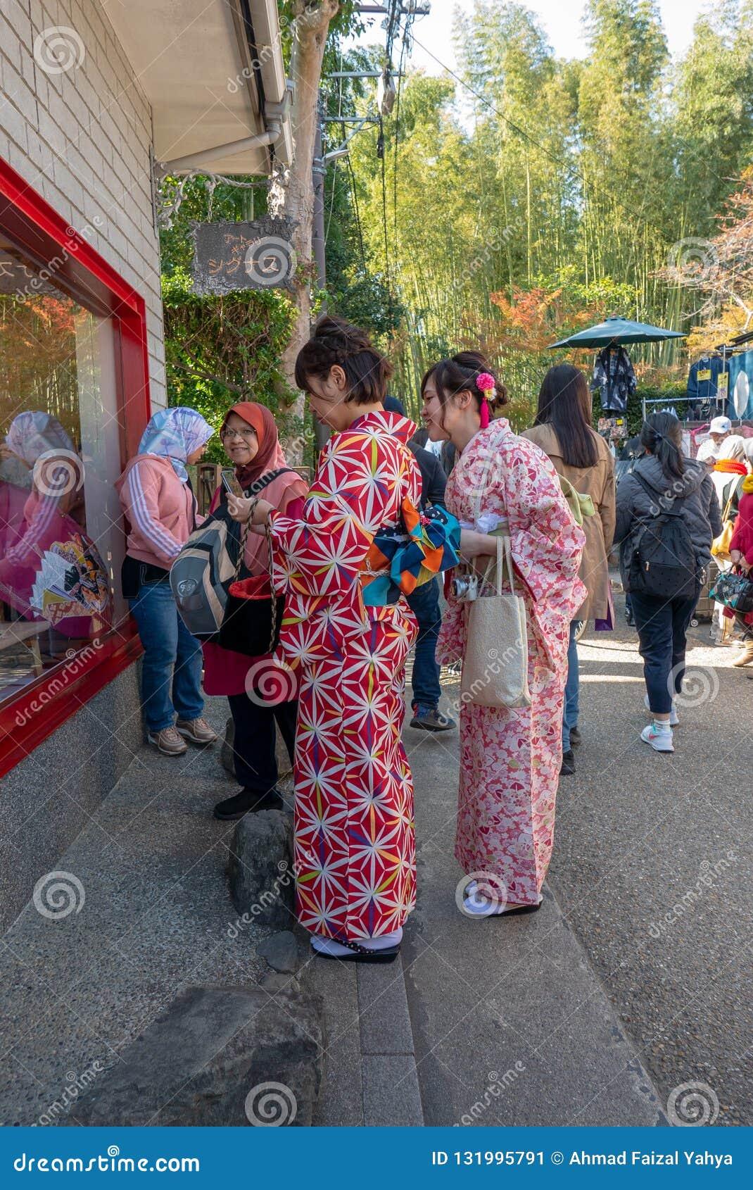 在和服礼服和两三名回教妇女的未认出的东瀛女人背景窗口商店的