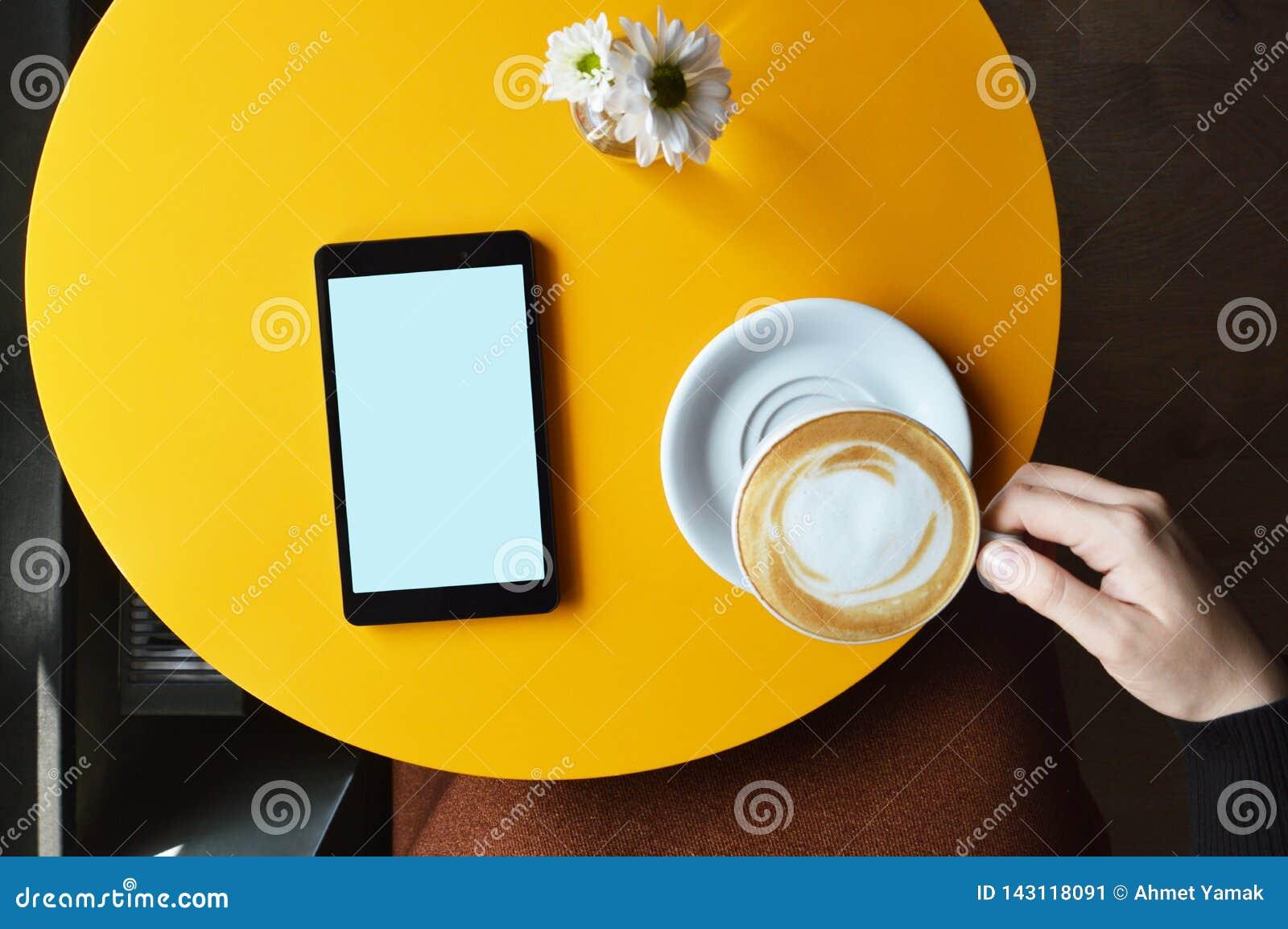 在咖啡馆桌和一杯妇女手藏品咖啡的数字片剂顶部