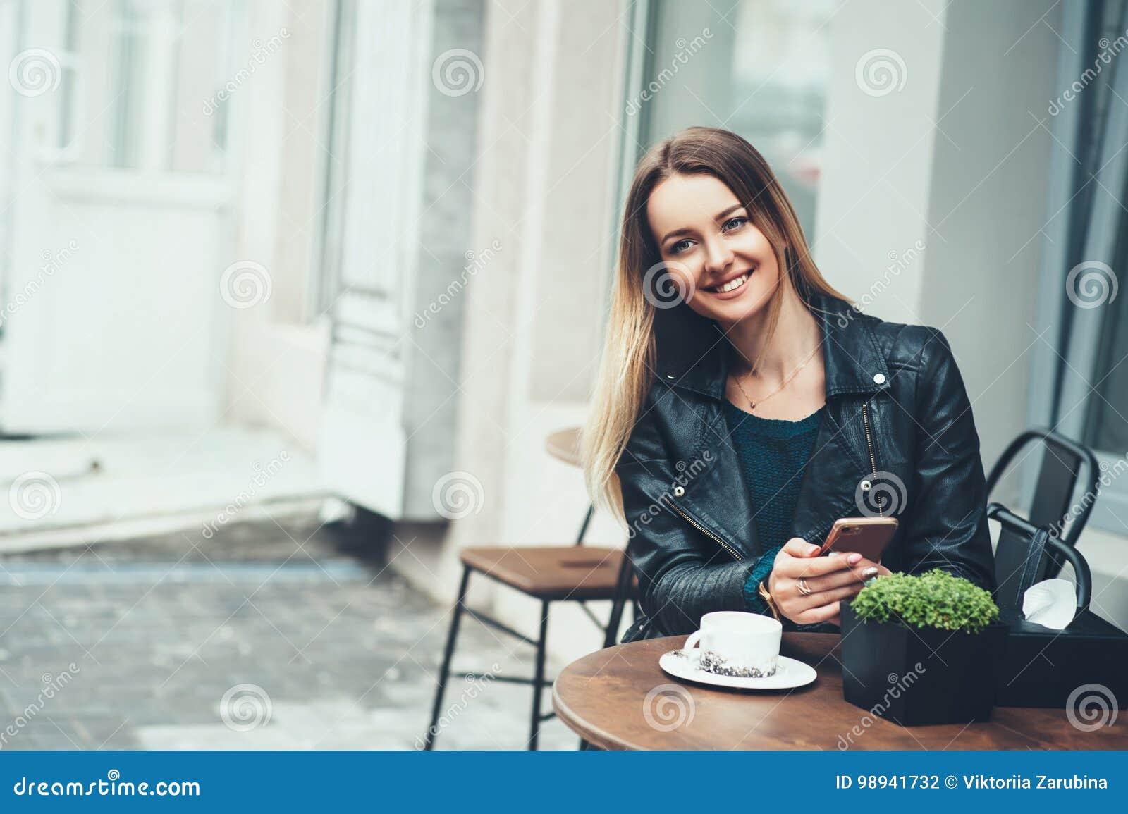 在咖啡馆的无忧无虑的时间 有坐在咖啡馆室外和键入的快的消息的微笑的可爱的少妇