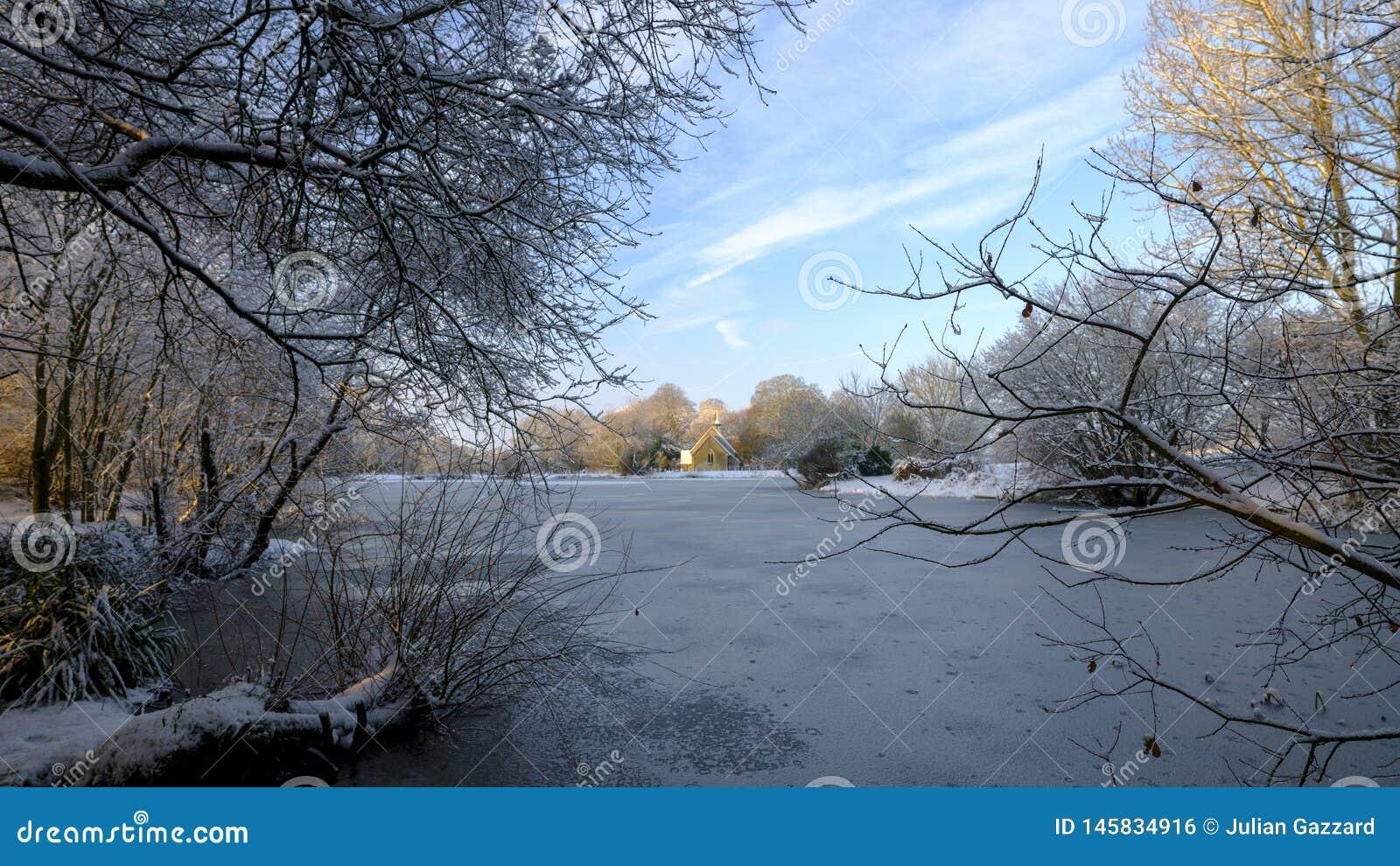 在哈特利Mauditt池塘的结冰的冬天场面圣伦纳德的教会的,南下来国立公园,汉普郡,英国