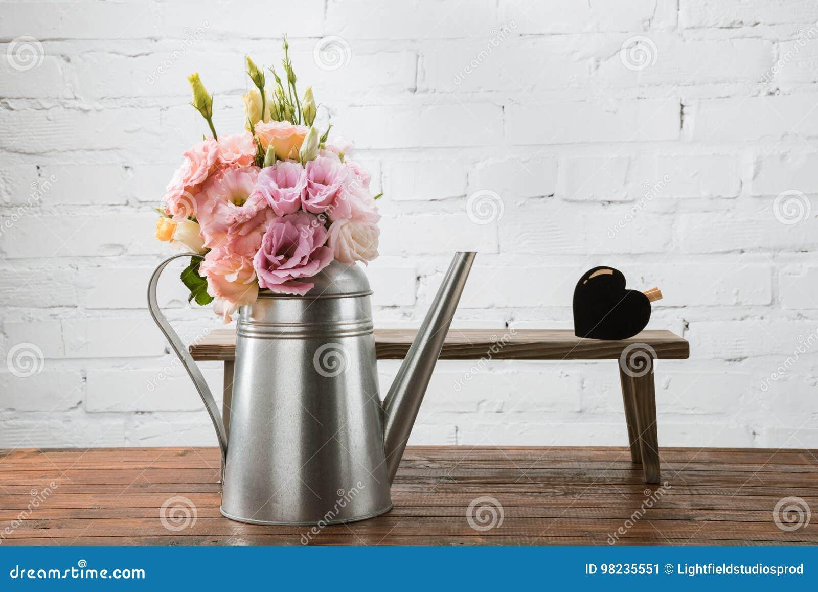 在喷壶和小长凳的嫩花与心脏标志安排了木表面上
