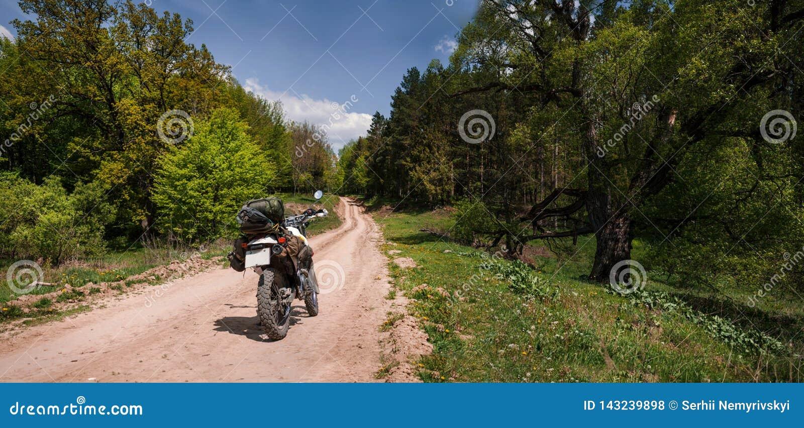 在土森林公路,enduro,活跃生活方式,旅行恋人概念的冒险摩托车