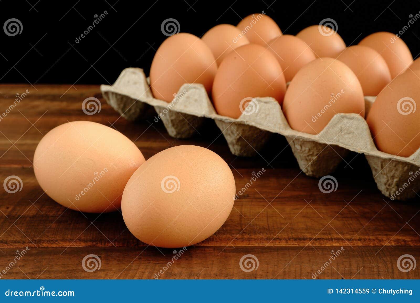 在土气木桌上的新鲜的鸡鸡蛋
