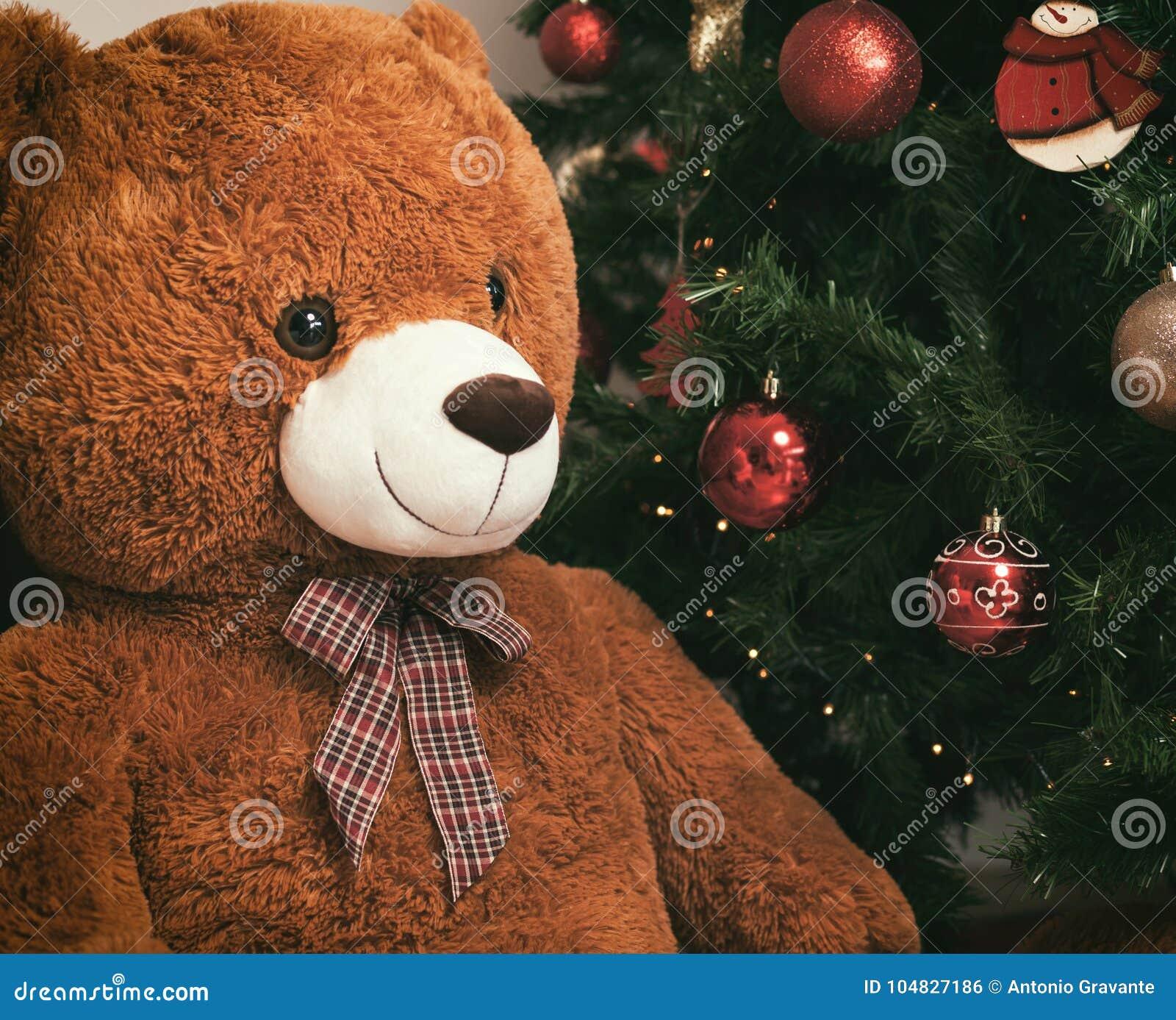 在圣诞树附近的玩具熊与礼物
