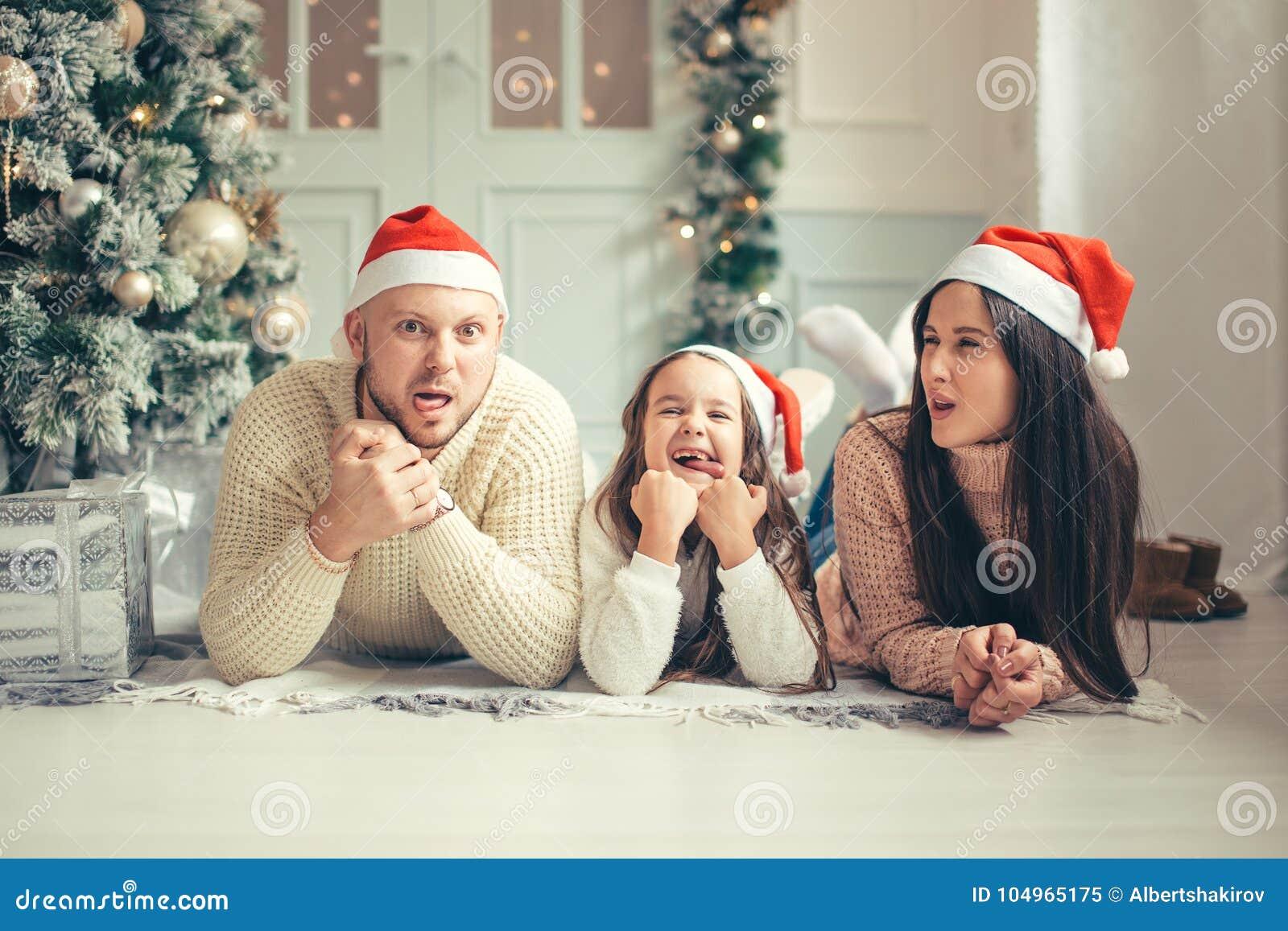 在圣诞节说谎在床上的圣诞老人帽子的家庭 获得母亲的父亲和的婴孩乐趣