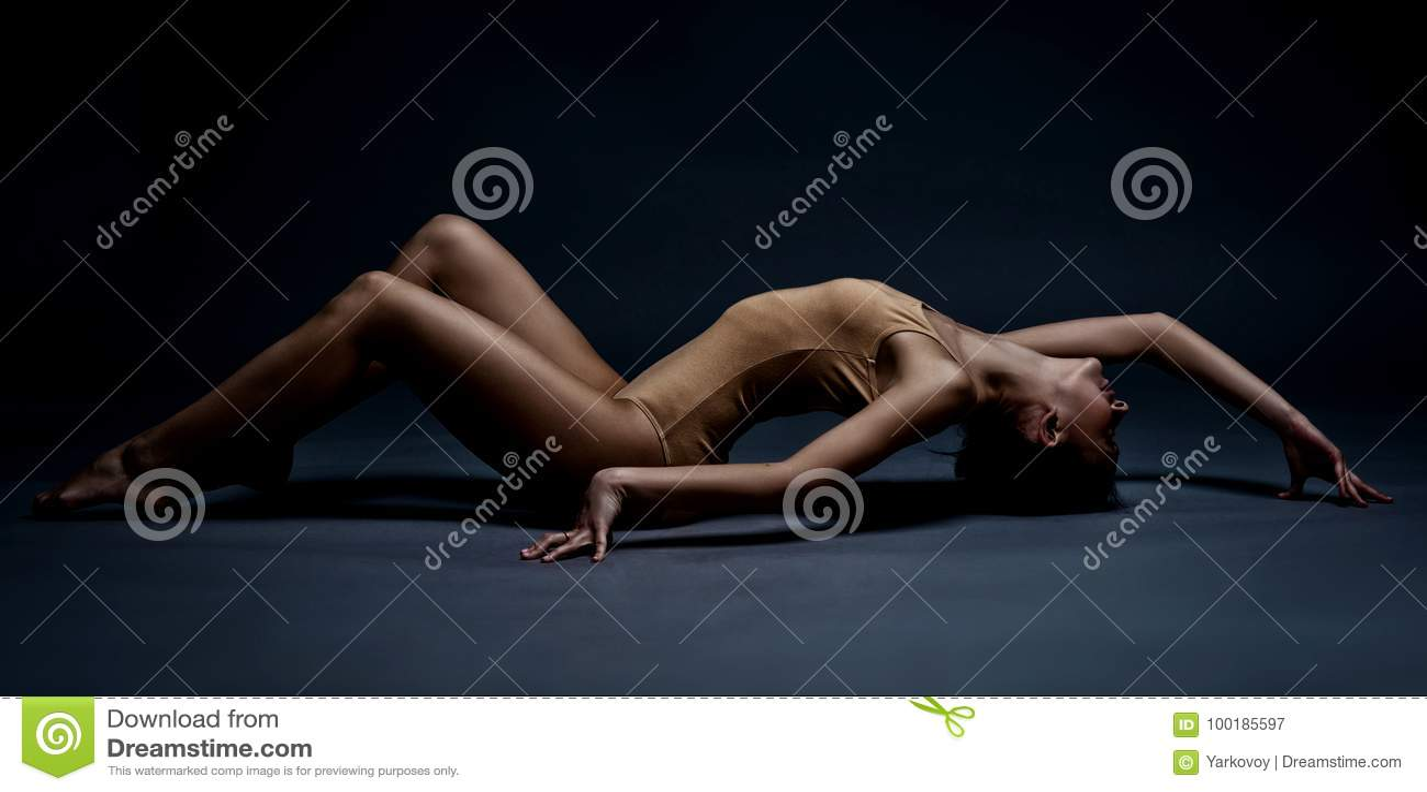在地板上的美丽的运动女孩 在行动的演播室画象