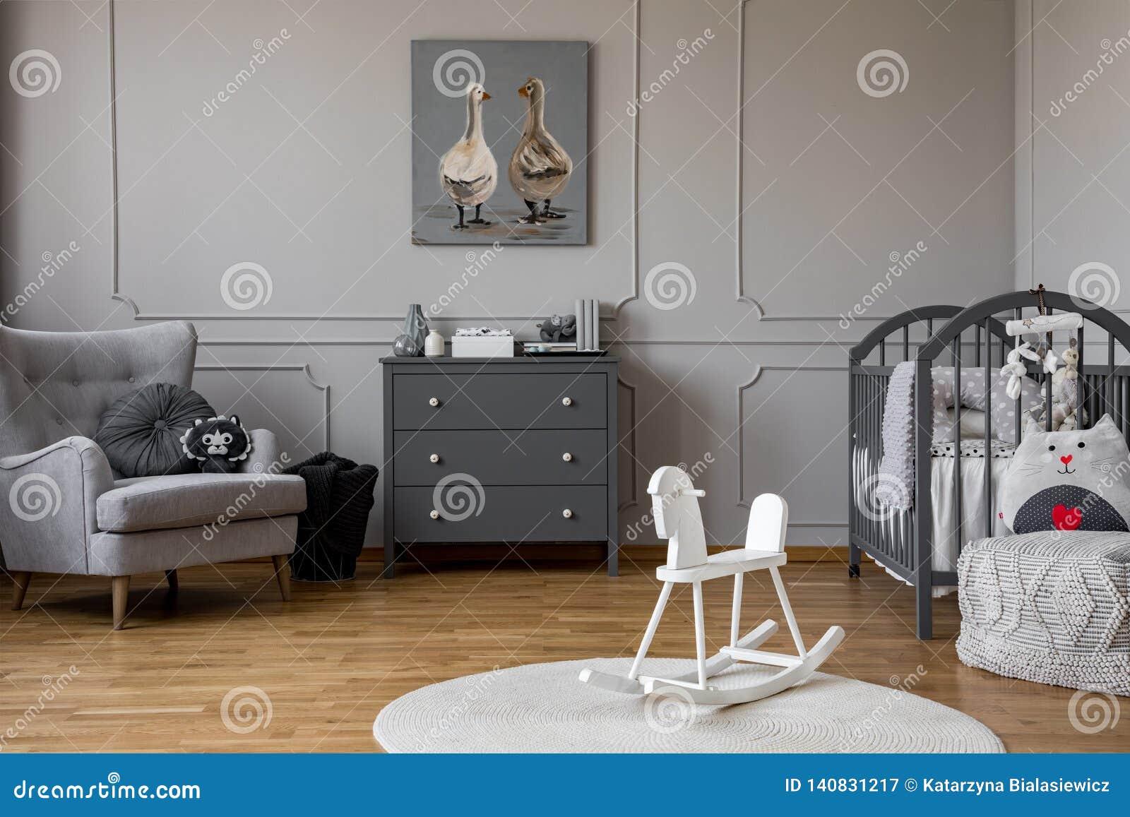 在地毯的白色摇马在灰色孩子的与海报的卧室内部在内阁上 实际照片