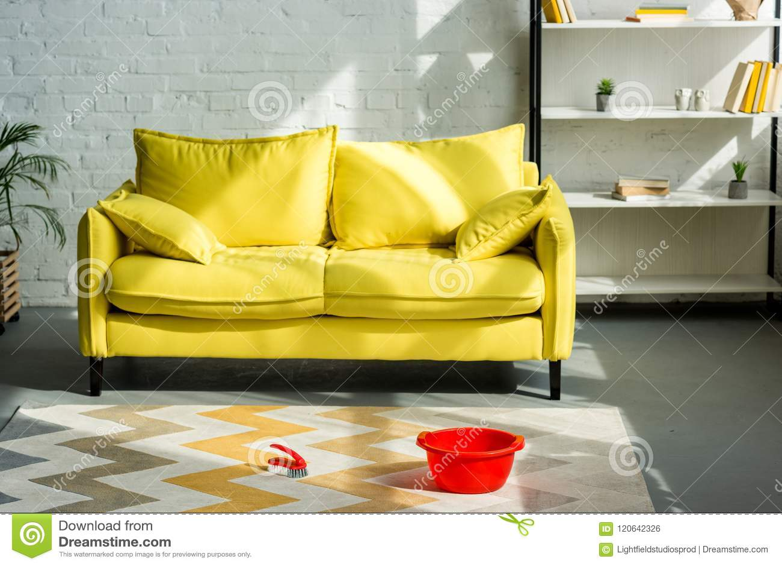 在地毯的红色桶和清洁刷在地板,黄色沙发上