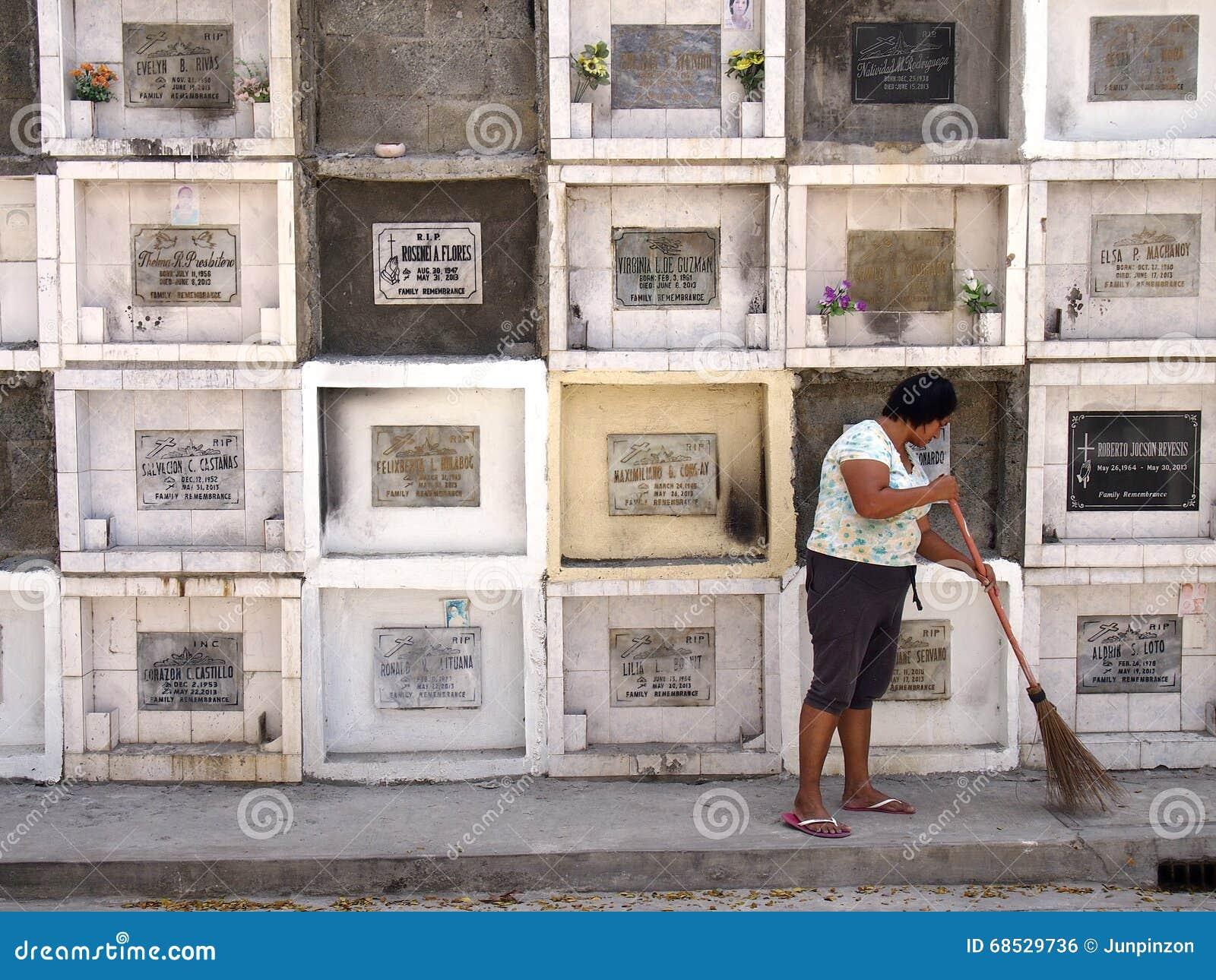 在坟墓前面的专栏的妇女打扫在一座公墓在安蒂波洛市,菲律宾