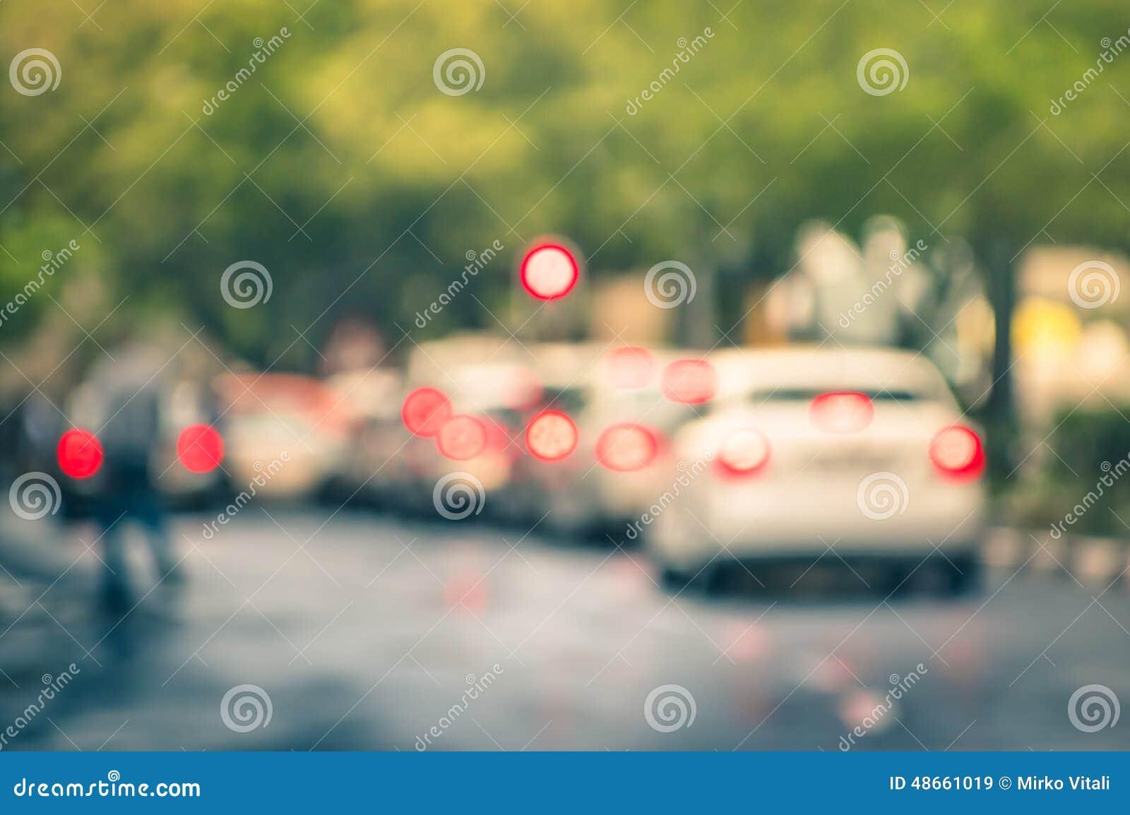 在城市交通的Defocused汽车在一个雨天阻塞