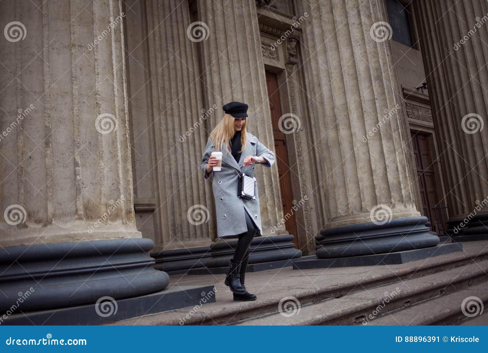 在城市附近用咖啡去的年轻人,熟悉内情和有吸引力白肤金发走,在事务看手表并且赶紧