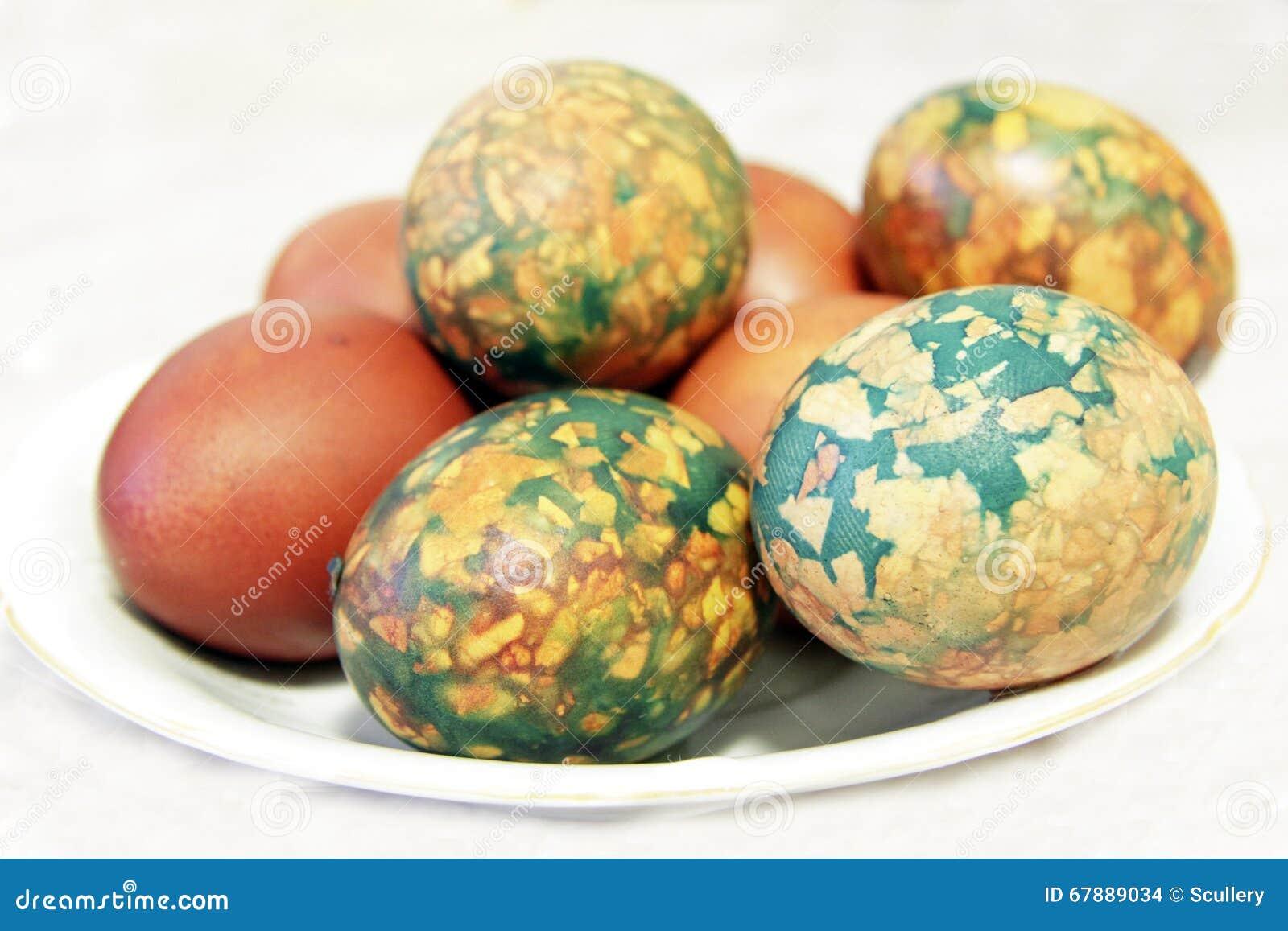 在堆安置的白色板材的五颜六色的复活节彩蛋