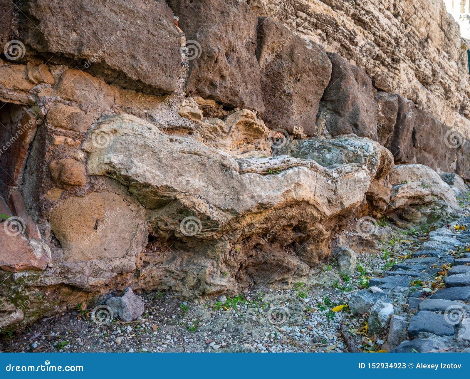 在堡垒墙壁的基地的古老石制品在蒂沃利,意大利
