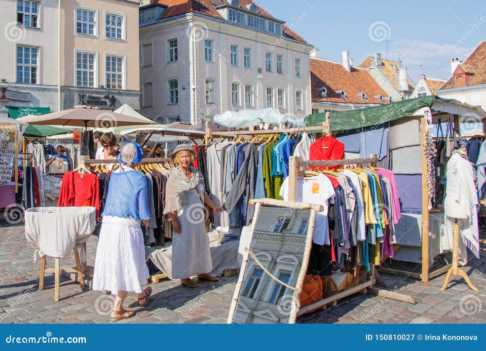 在塔林城镇厅正方形的市场  选择礼服的一个老妇人