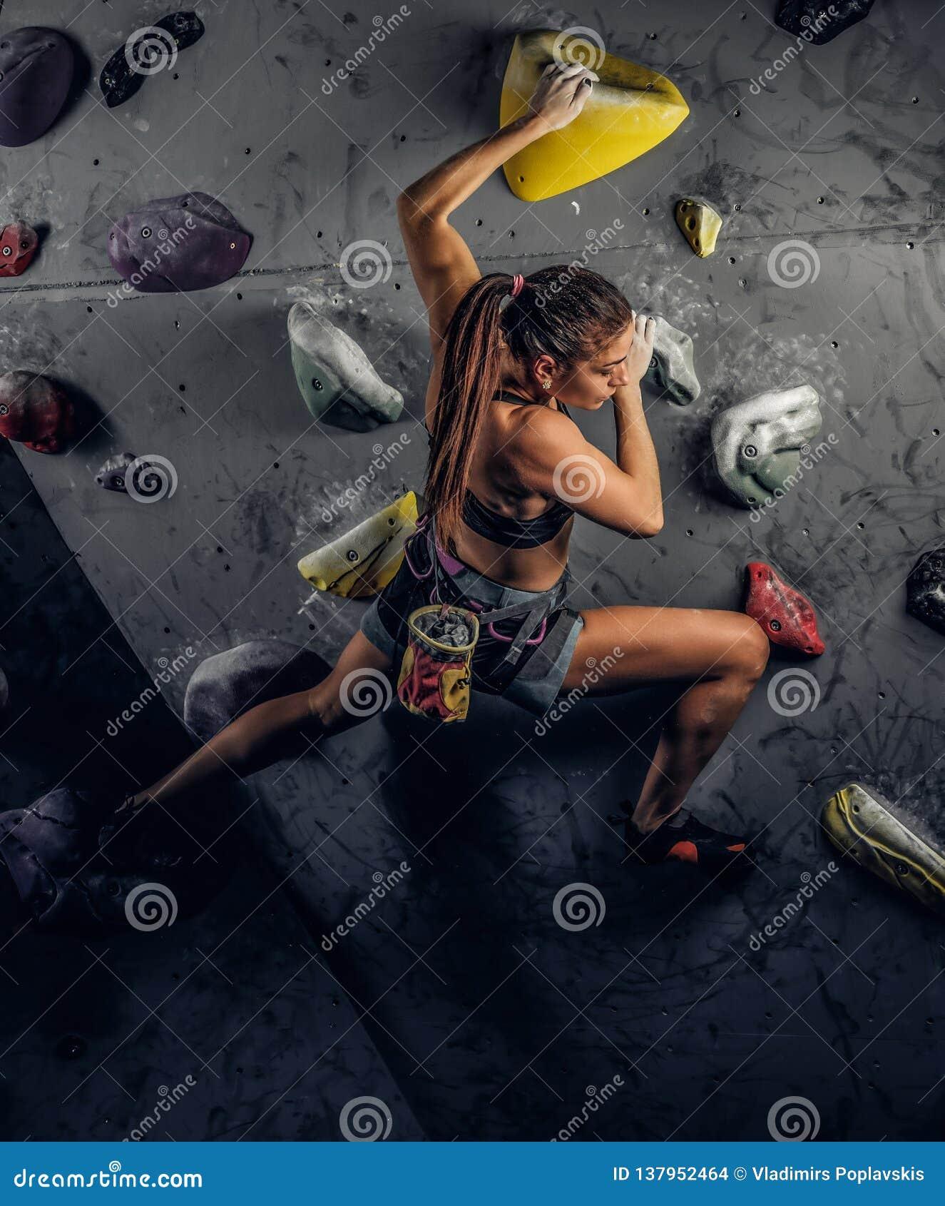 在墙壁上的年轻女人佩带的运动服实践的攀岩户内