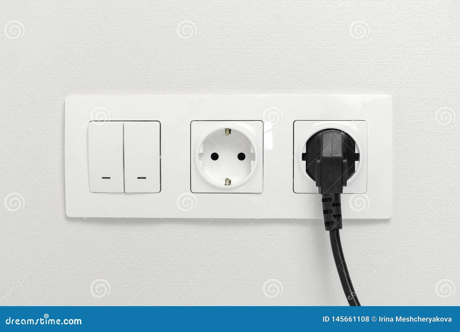 在墙壁上的电子插口有黑连接插头和白色开关的