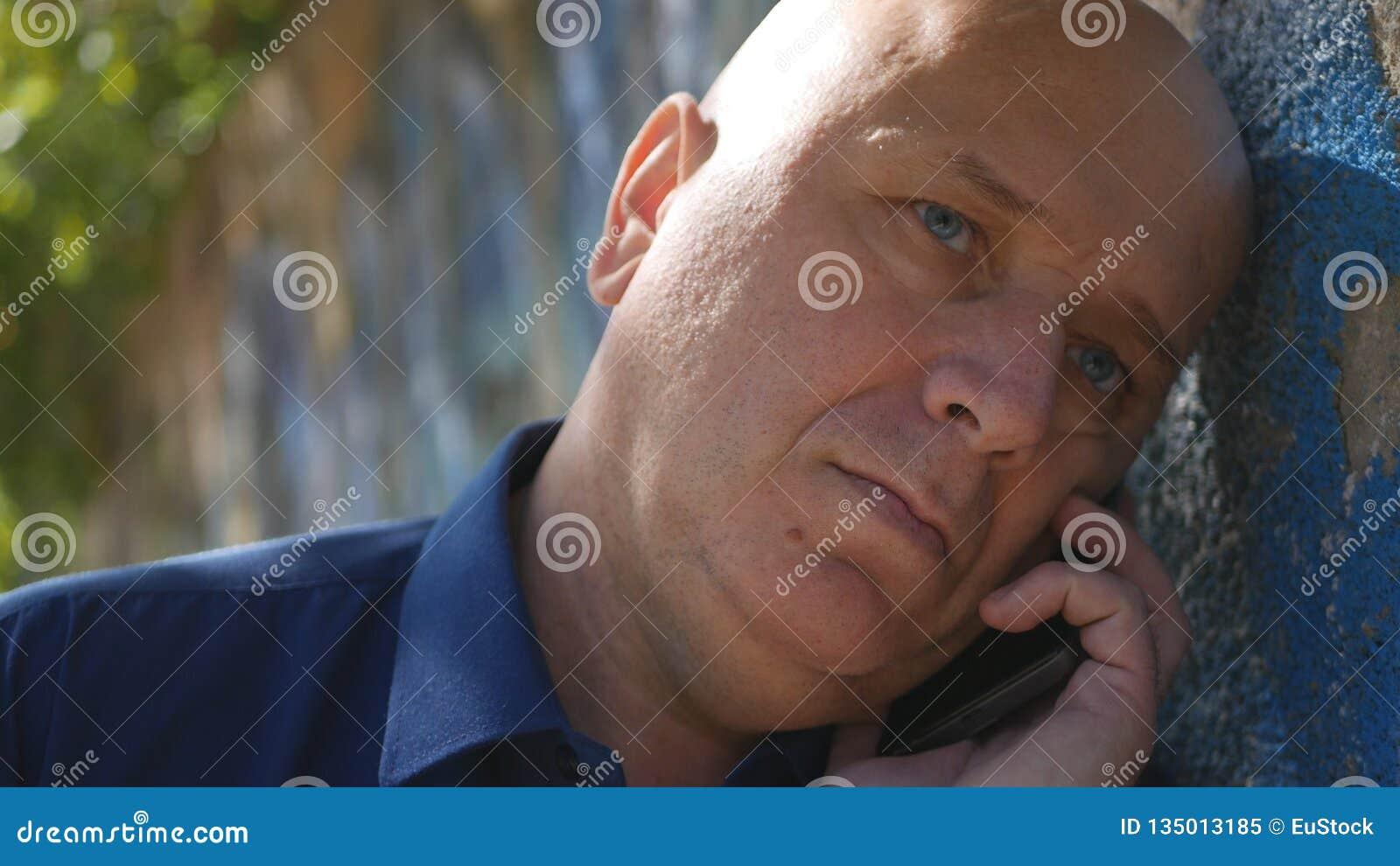 在墙壁附近的哀伤的人在创始电话的街道尝试