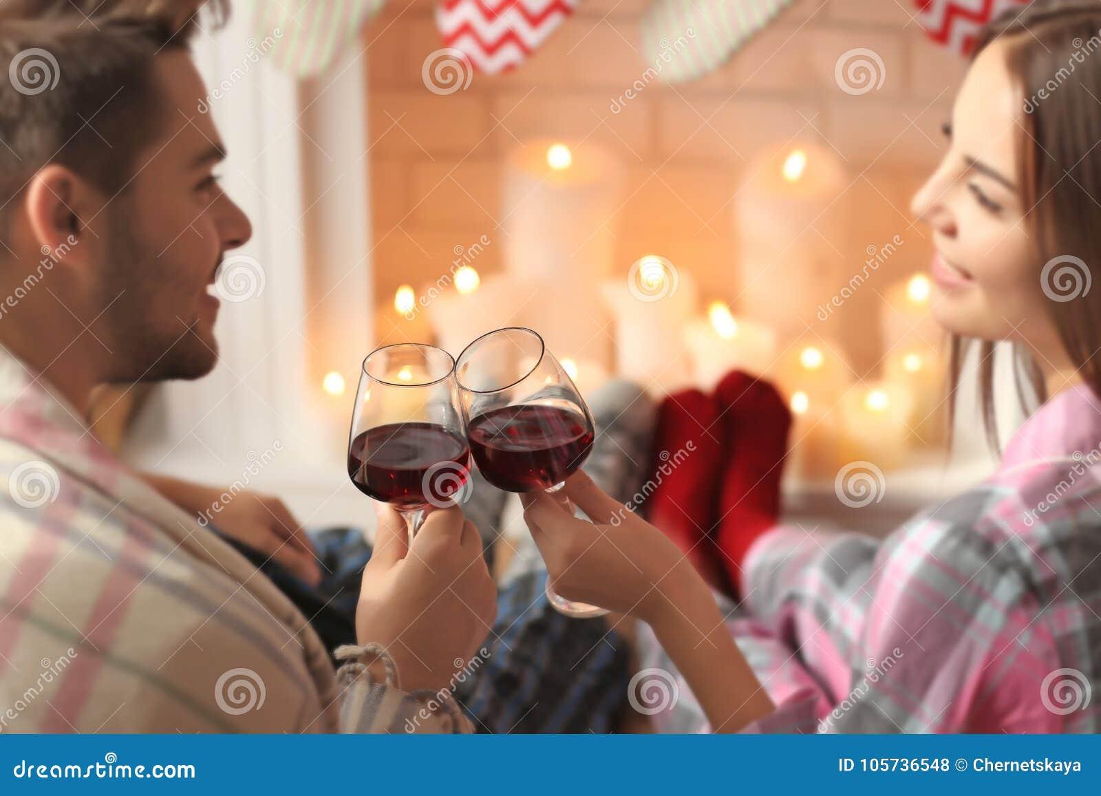 在壁炉前面的夫妇饮用的酒在家