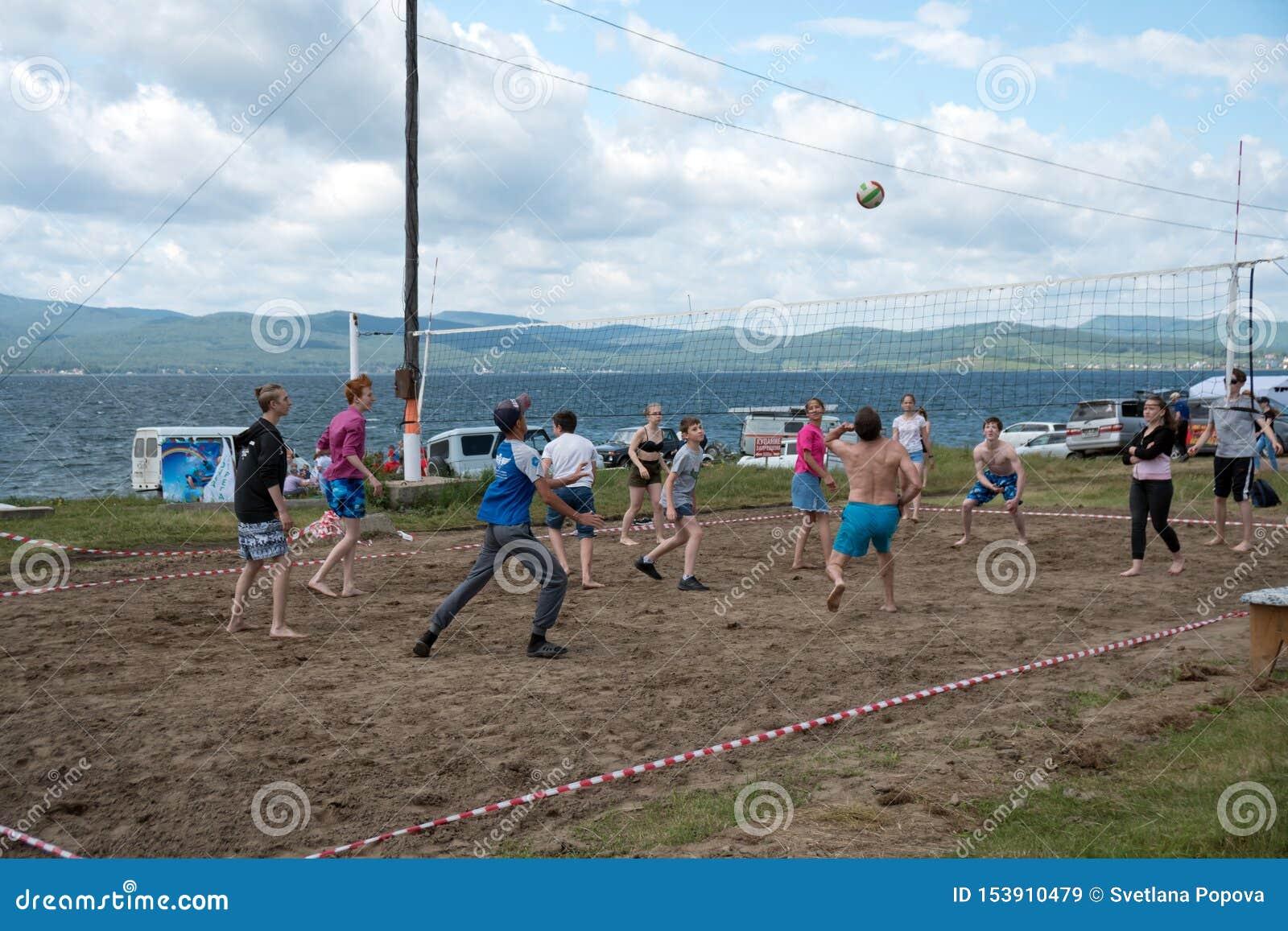 在夏天休假期间,少年打在海滩的排球,在一个大湖的岸