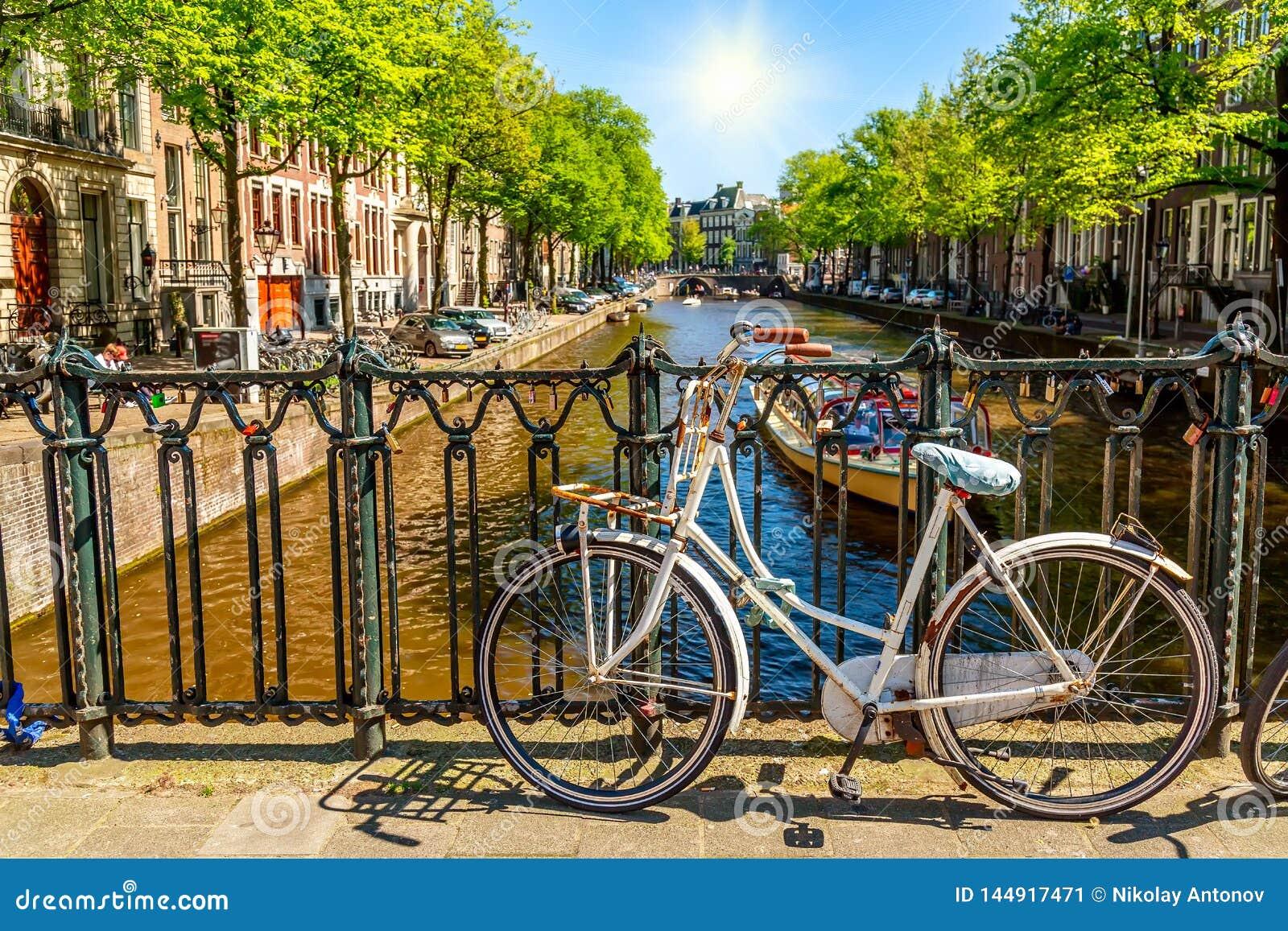 在夏天好日子期间,在桥梁的老自行车在阿姆斯特丹,反对一条运河的荷兰 阿姆斯特丹明信片偶象视图