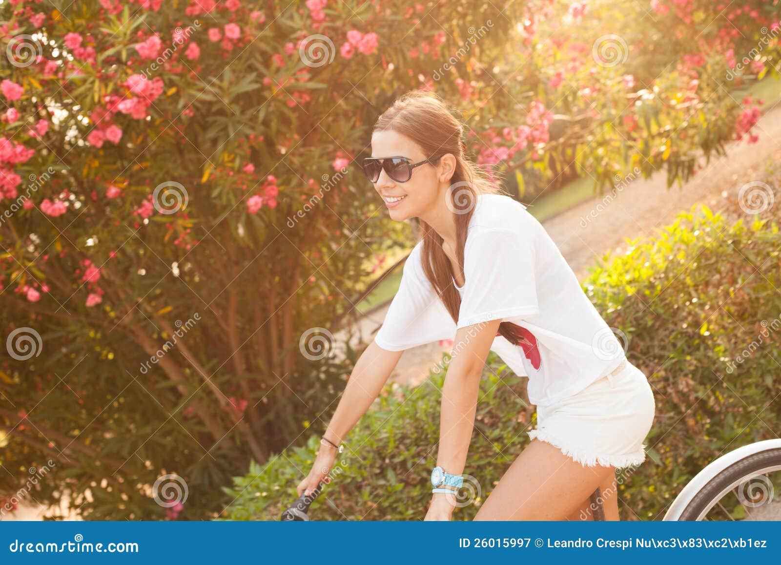 在夏天的新美好的妇女骑马bicicle