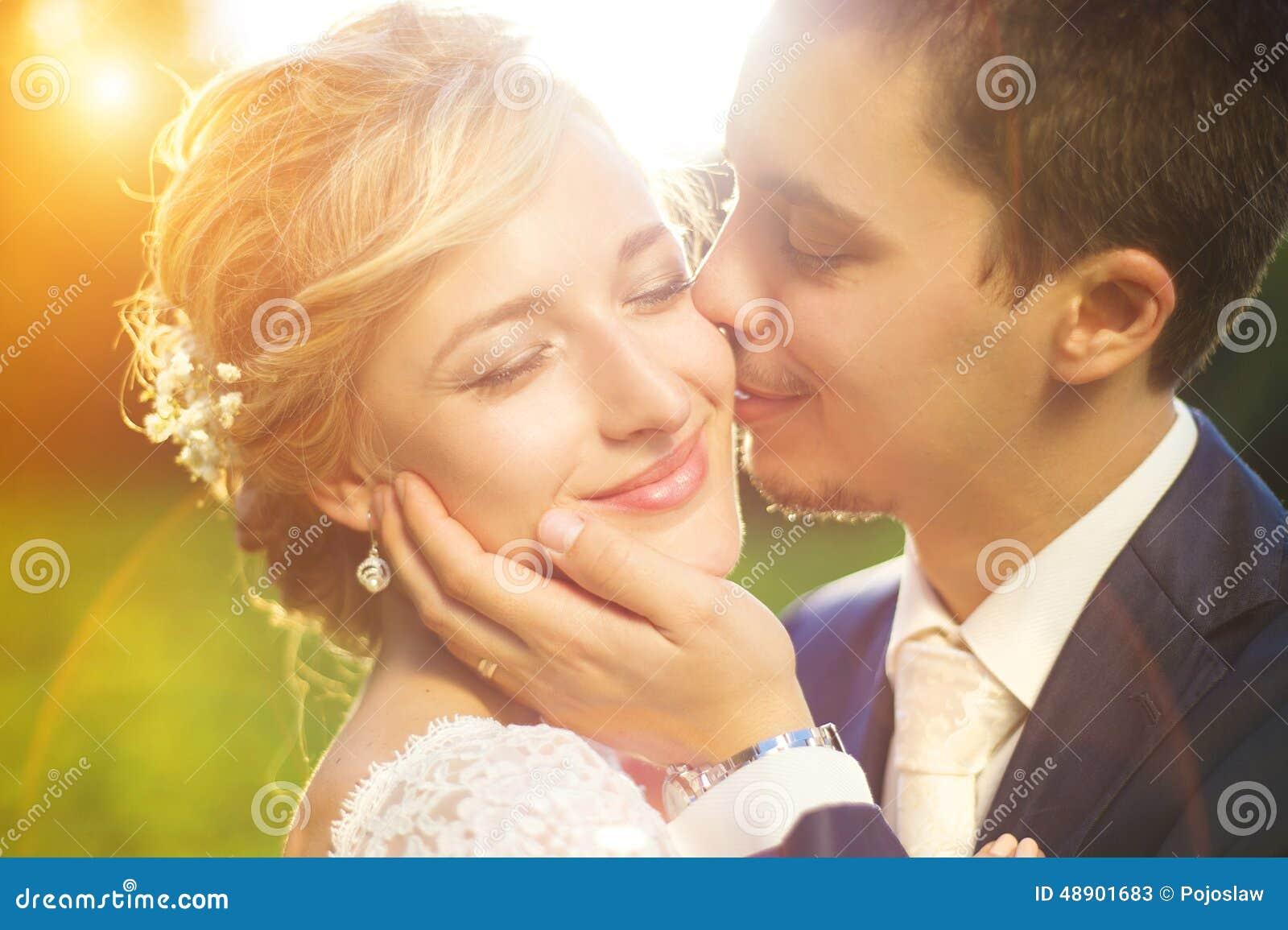 在夏天草甸的年轻婚礼夫妇