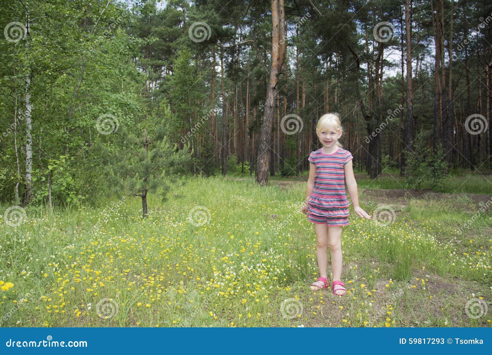 夏天明亮的晴天站立在花草甸的森林的一个小女孩.图片