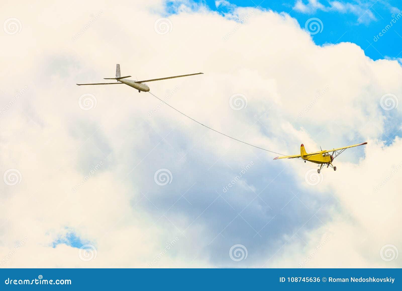 在多云天空的黄色小轻引擎体育飞机飞行在绳索滑翔机飞机上拉扯