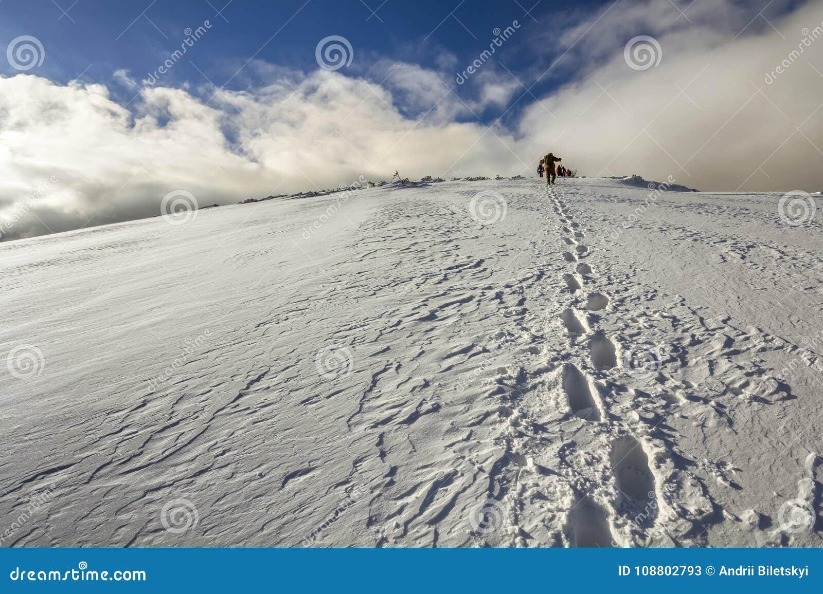 在多雪的走与在山的背包的小山与脚印和很远远足者的宽看法