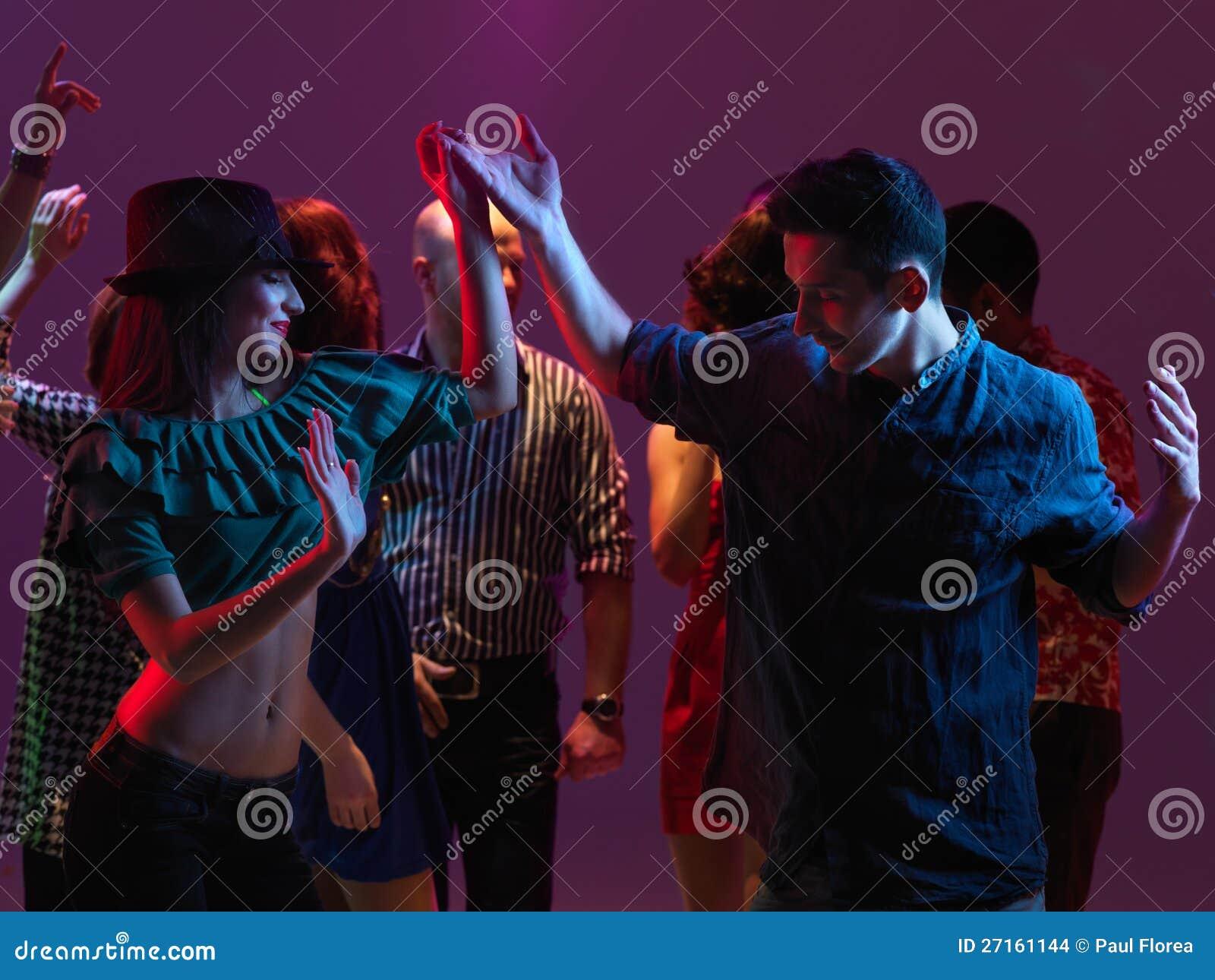 在夜总会的愉快的青年人跳舞