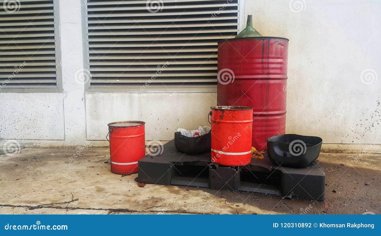 在大厦之外的肮脏的油腻桶与油膏滚磨 Disposed使用了在桶盖子的油