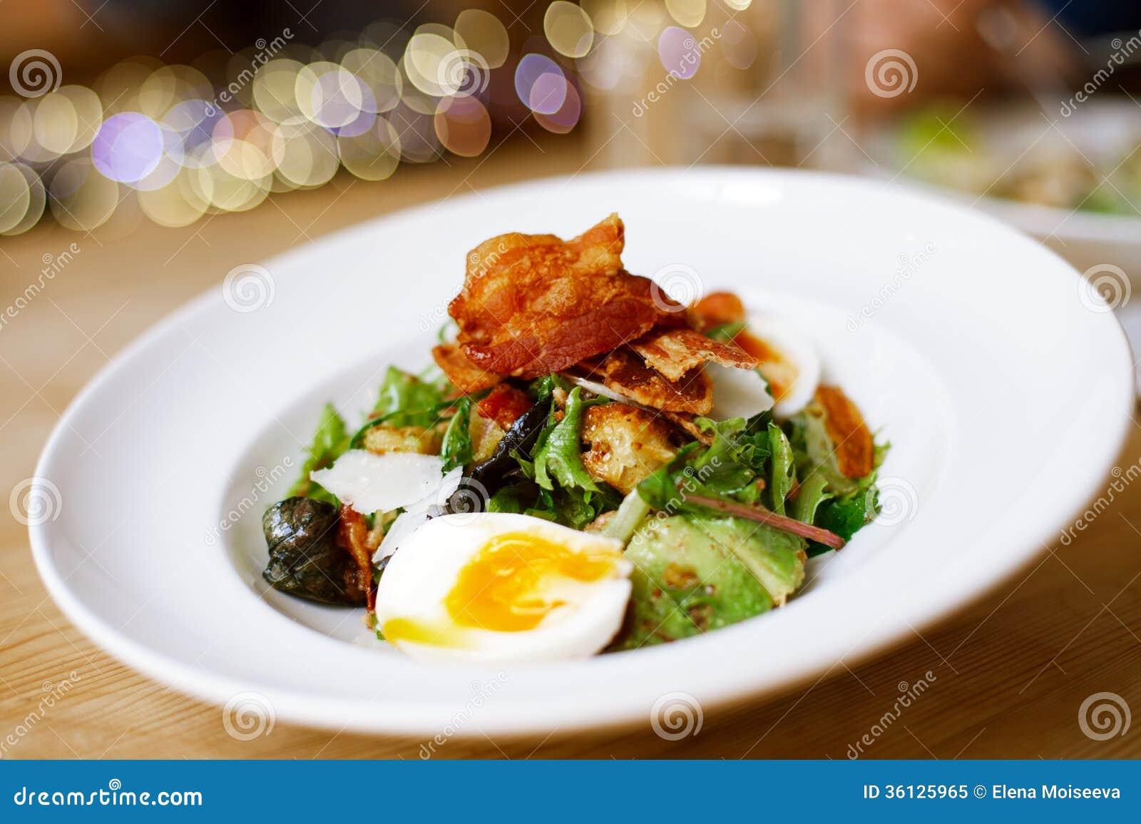 在大板材的烟肉和鸡蛋沙拉在桌上