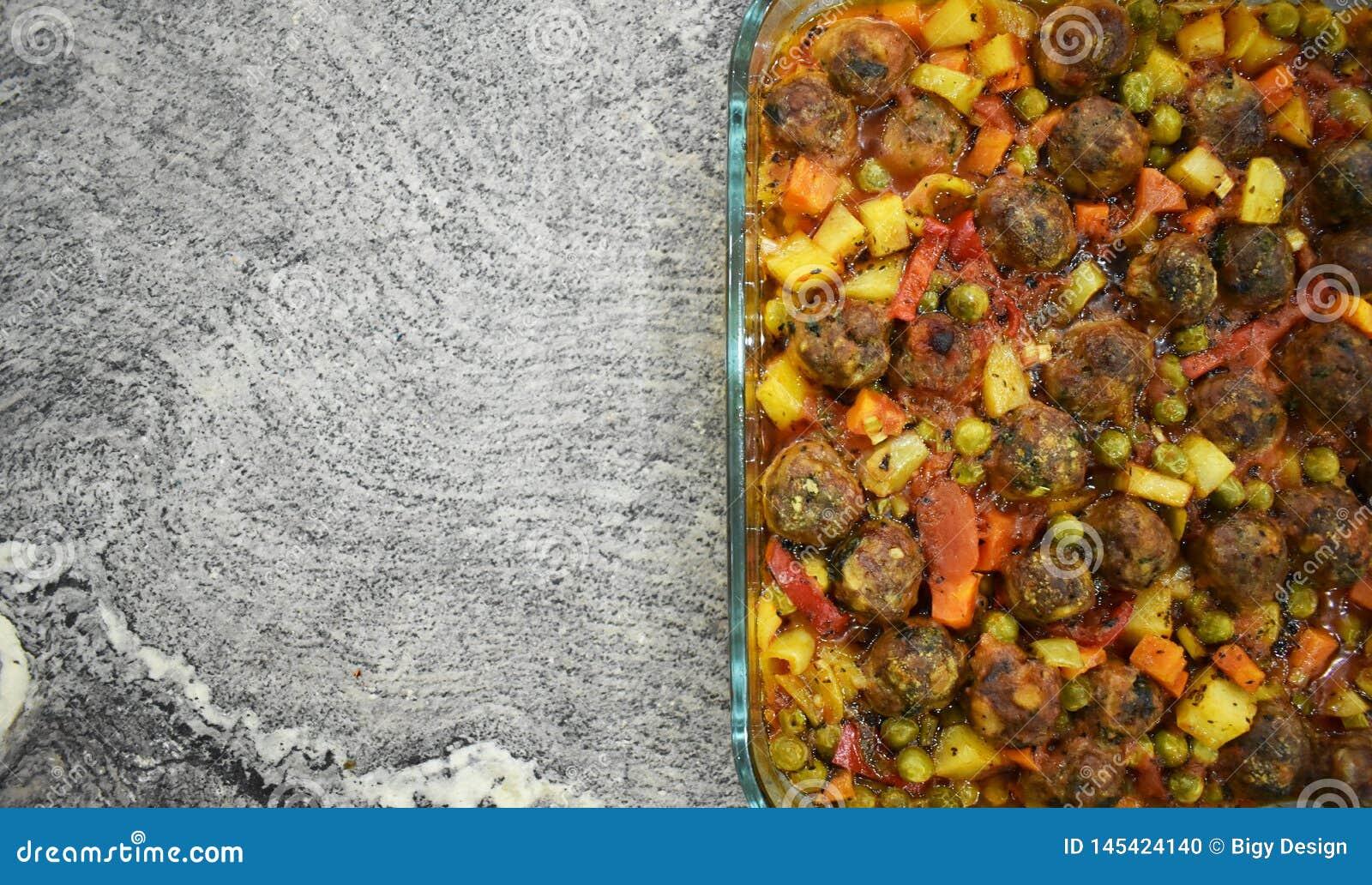 在大理石地板上,与菜的丸子,在玻璃烘烤的盘