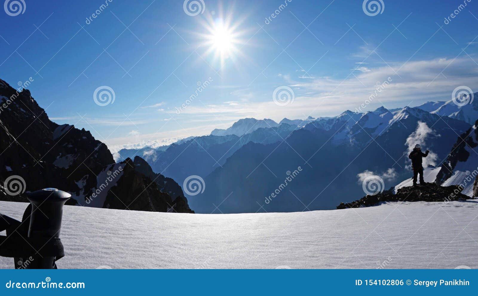 在太阳、多雪的山、天空蔚蓝和云彩的背景的迁徙的杆