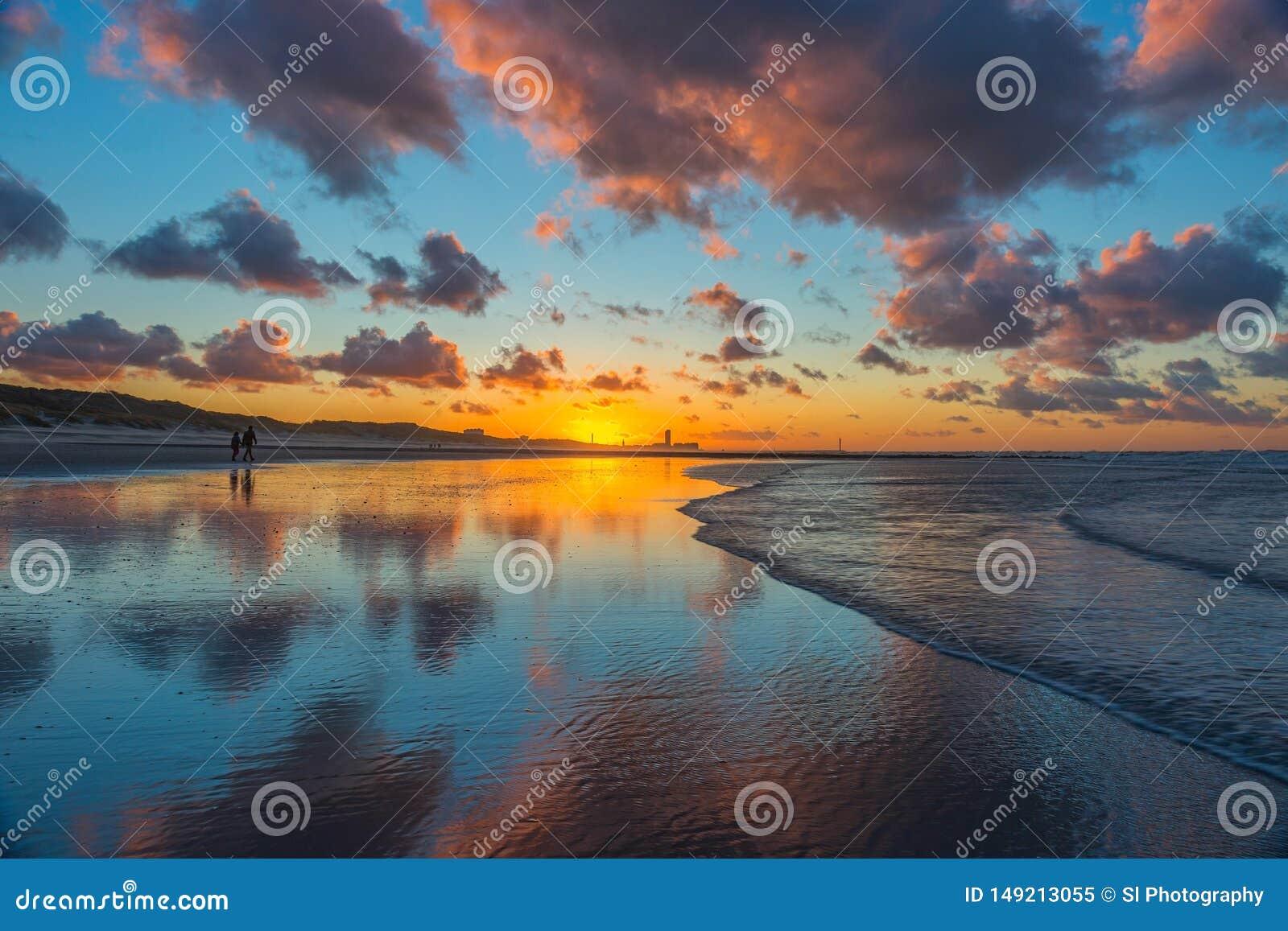 在奥斯坦德海滩的步行在日落,比利时