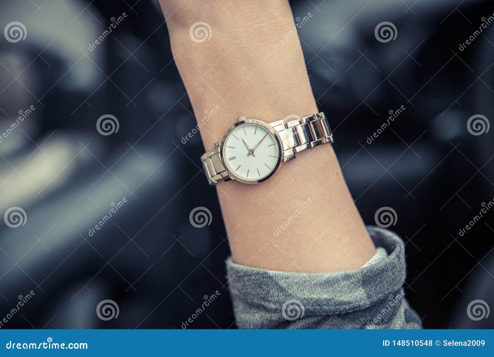 在女孩的手上的妇女的手表 妇女的金表 E