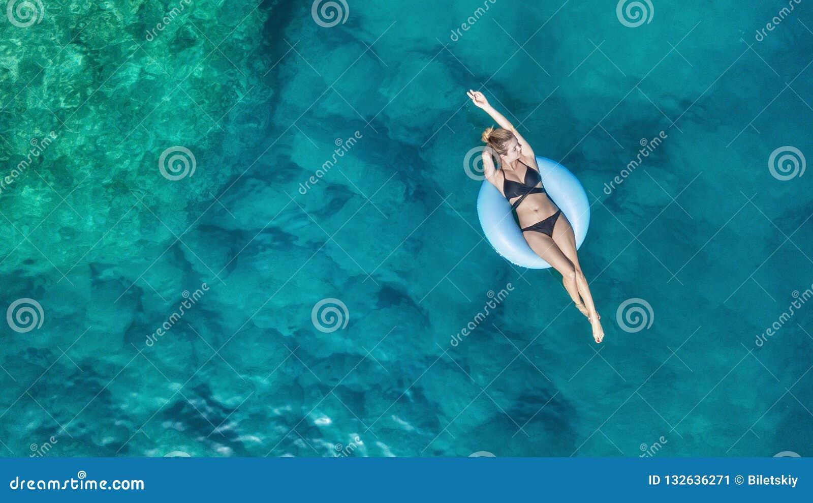 在女孩的鸟瞰图在海 从空气的绿松石水作为从空气的背景