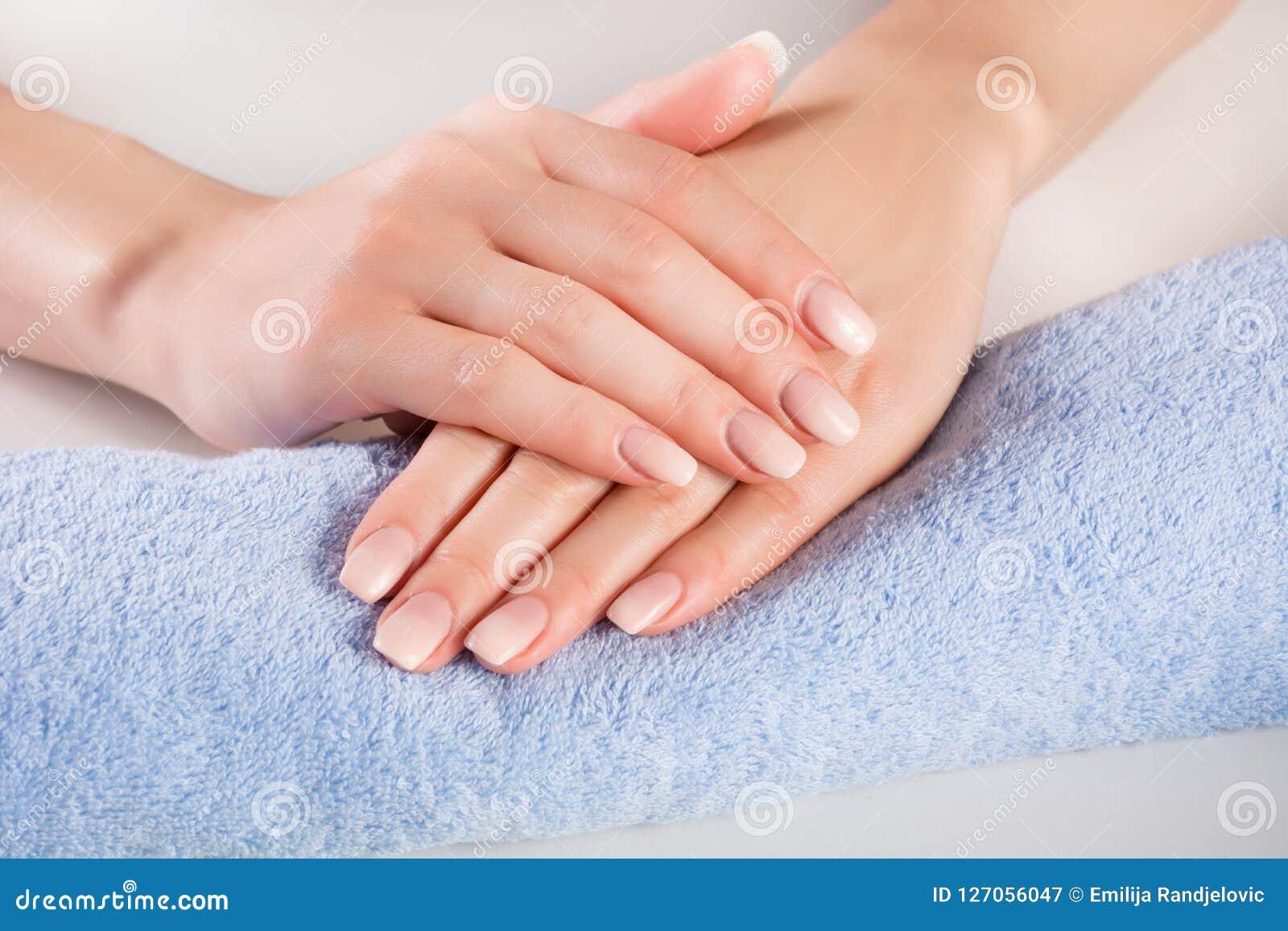 在妇女手上的Ombre法国钉子在柔和蓝色毛巾
