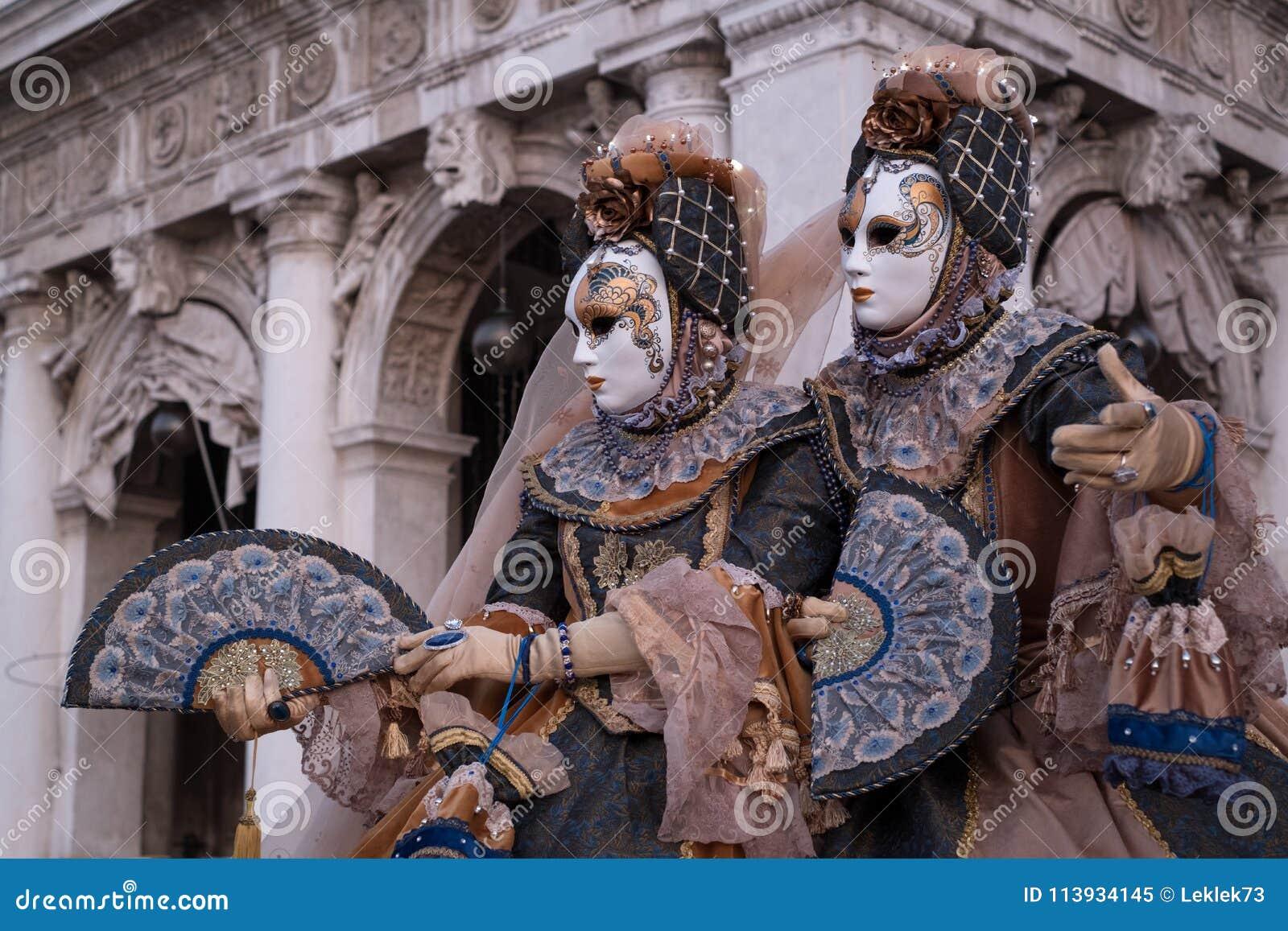 在威尼斯狂欢节期间,在服装的两个面具,当装饰的爱好者,站立在曲拱前面在圣指示正方形