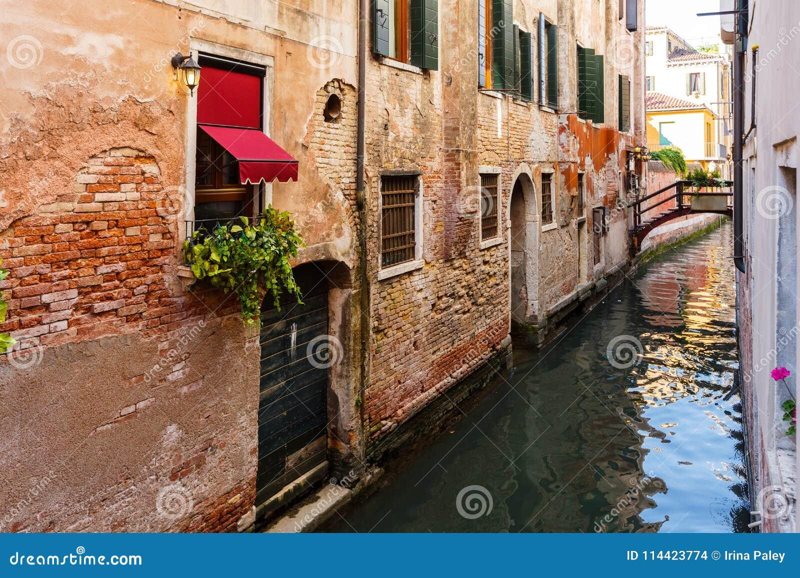 在威尼斯运河的典型的微小的桥梁 在窗口的花与威尼斯式快门