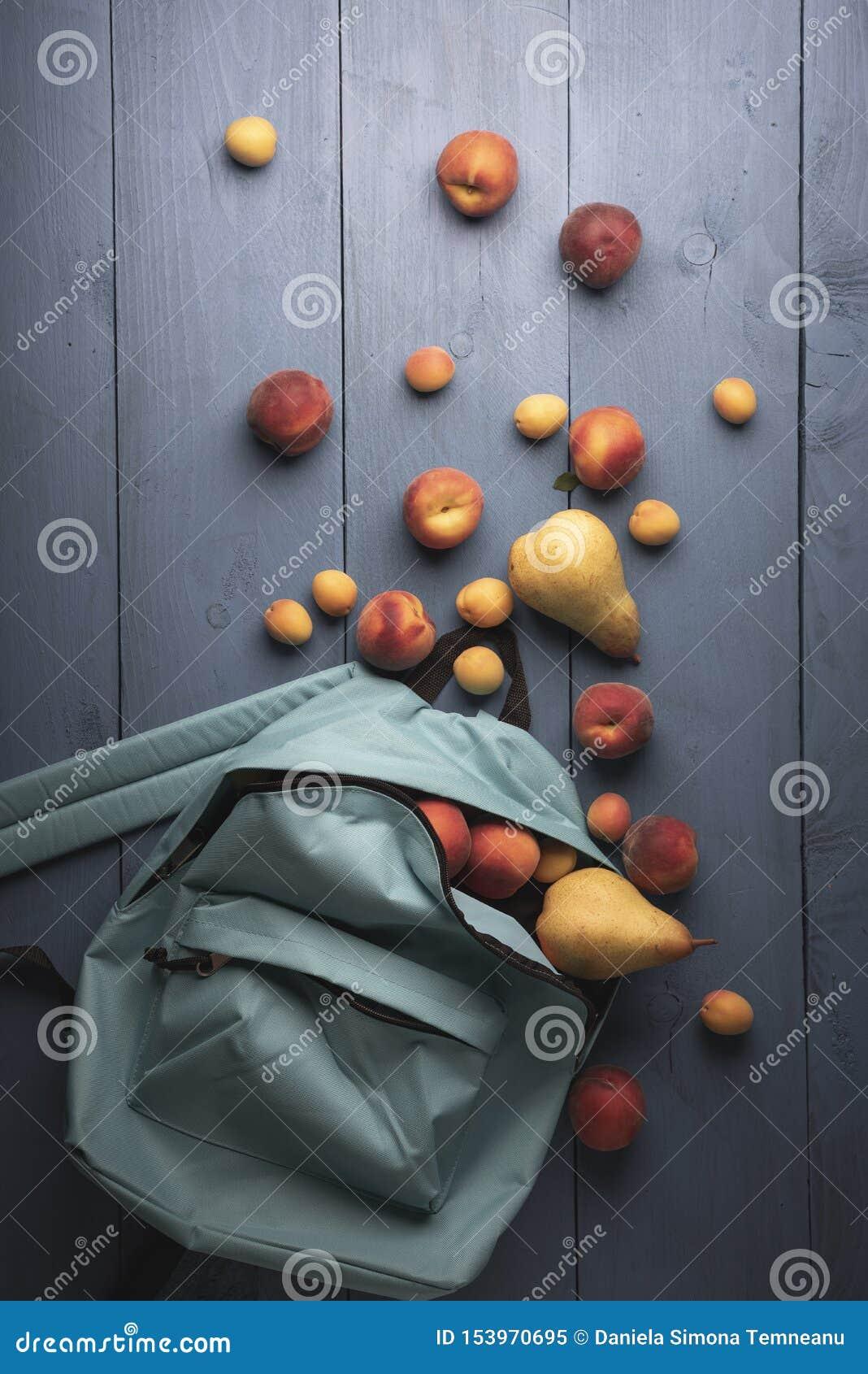 在学校背包的有机果子 成熟桃子、杏子和梨