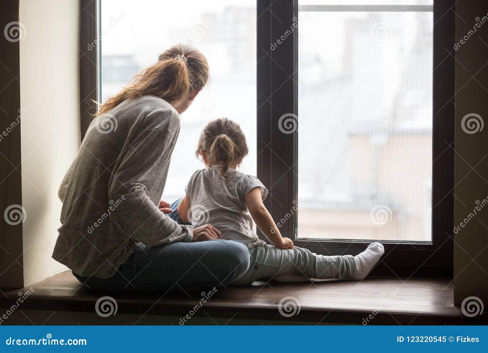 在孩子女儿和母亲的背面图坐基石