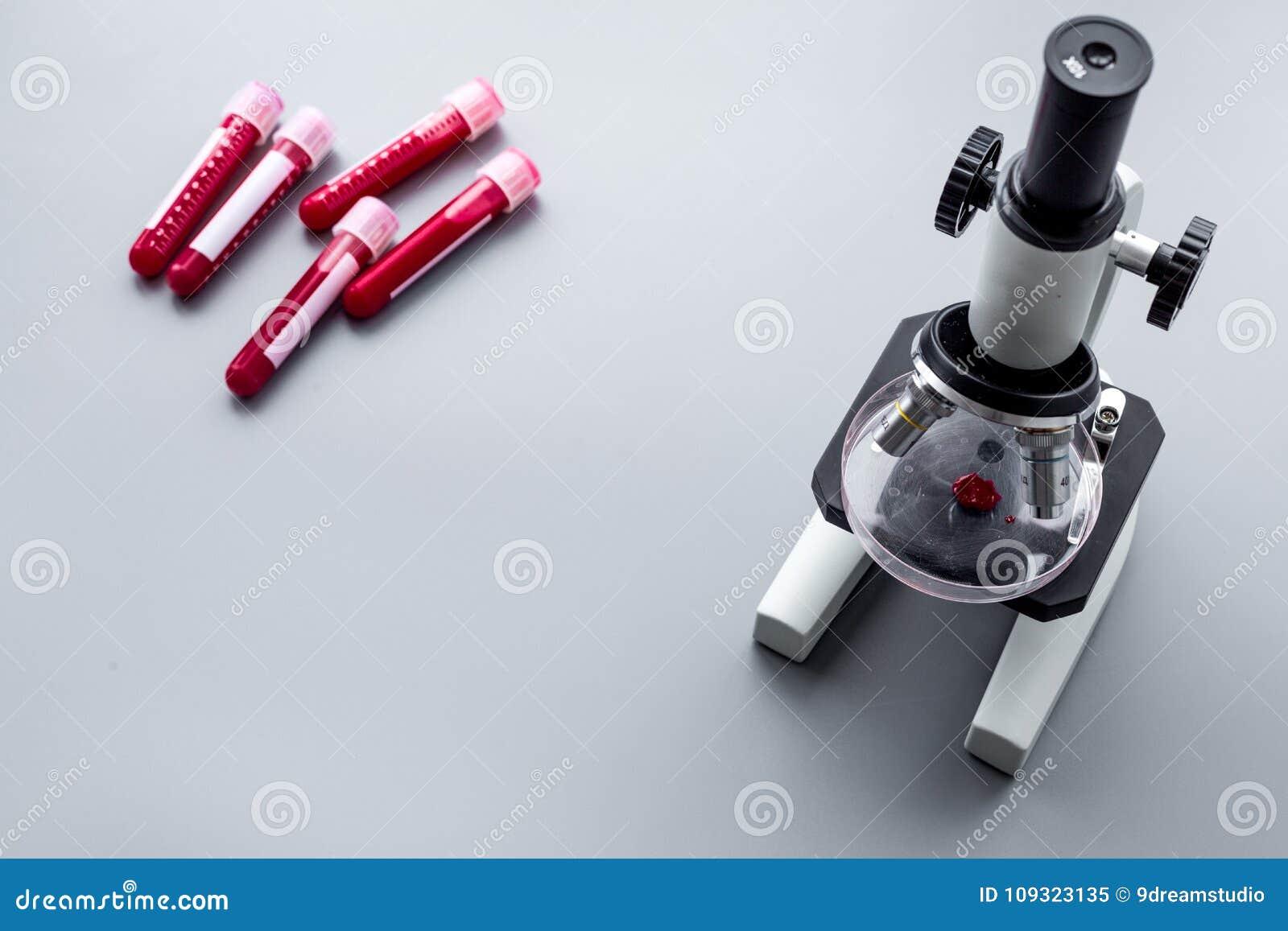 在实验室做验血 无政府主义 在试管的血样在灰色背景顶视图的显微镜附近复制