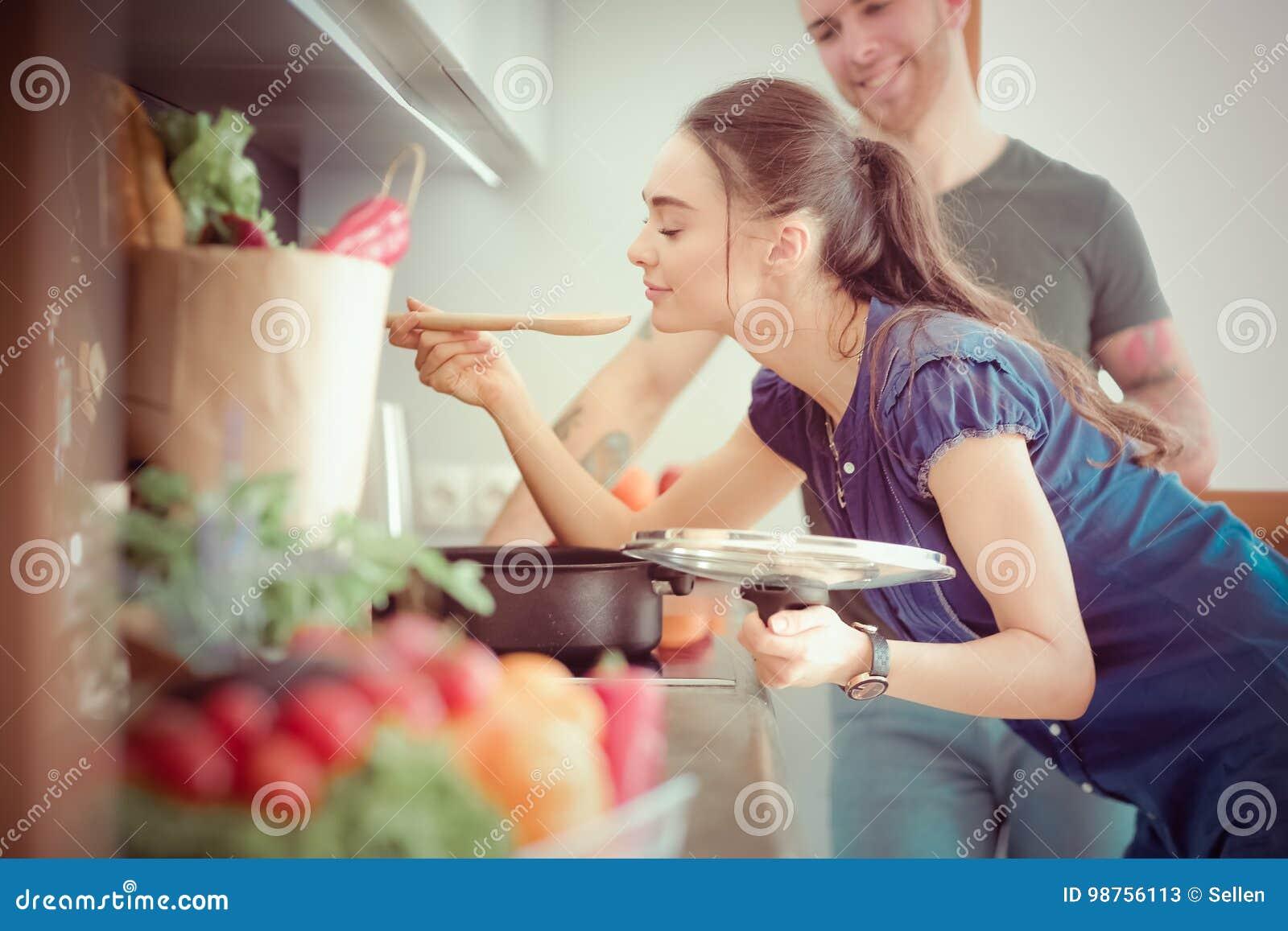 在家一起烹调在他们的厨房里的夫妇