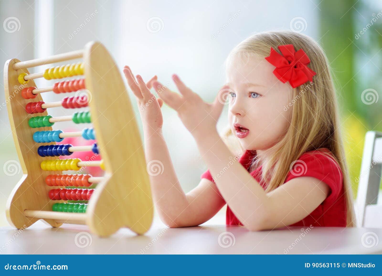 在家使用与算盘的逗人喜爱的小女孩 学会聪明的孩子计数