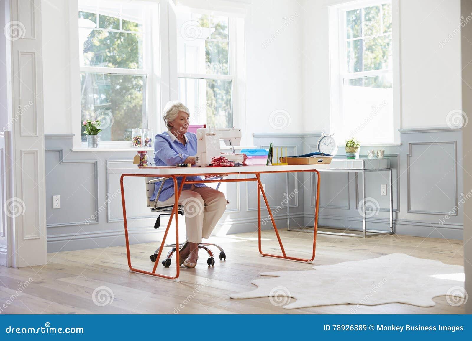在家做衣裳的资深妇女使用缝纫机