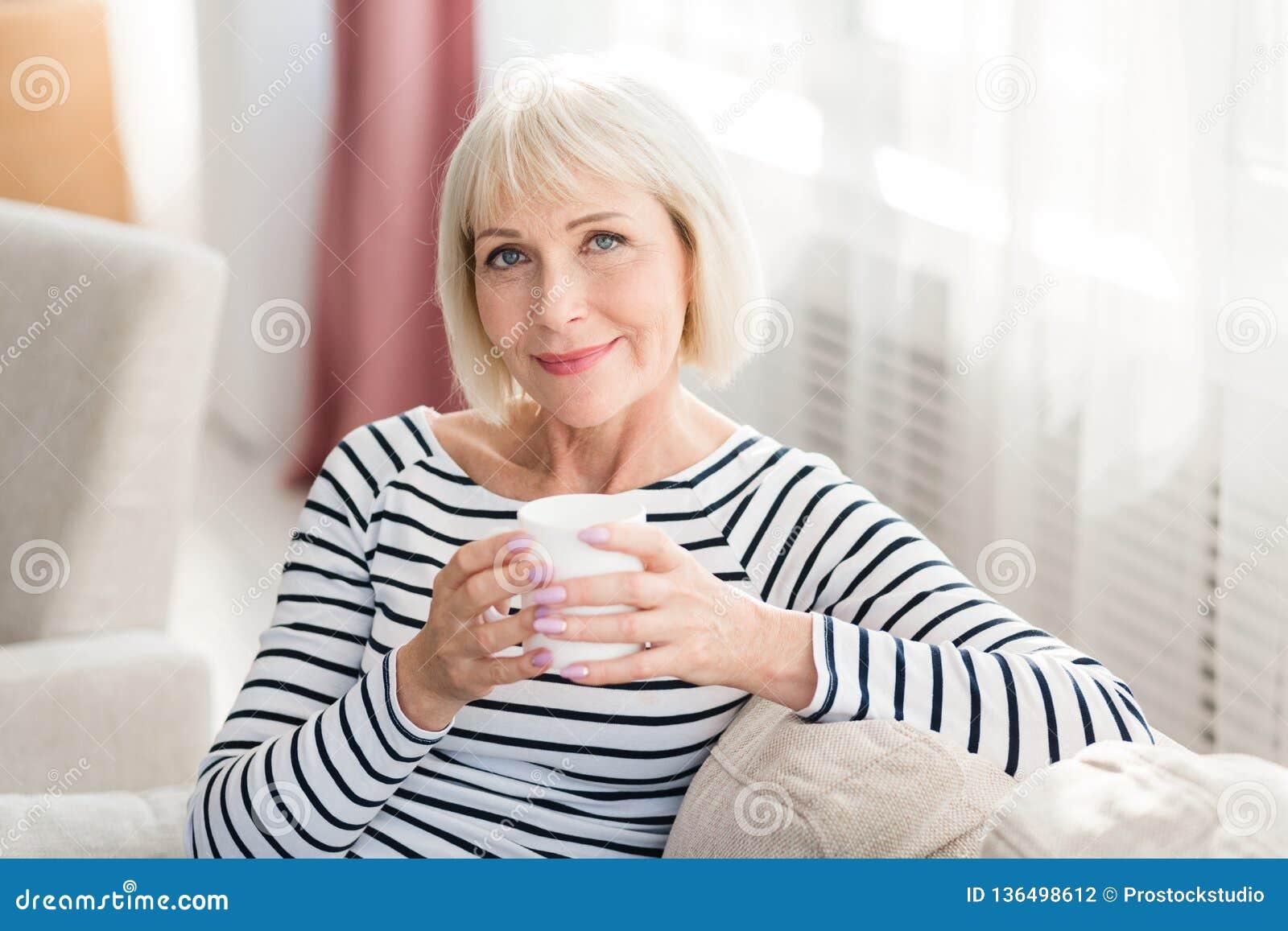 在家喝新鲜的早晨咖啡的成熟妇女
