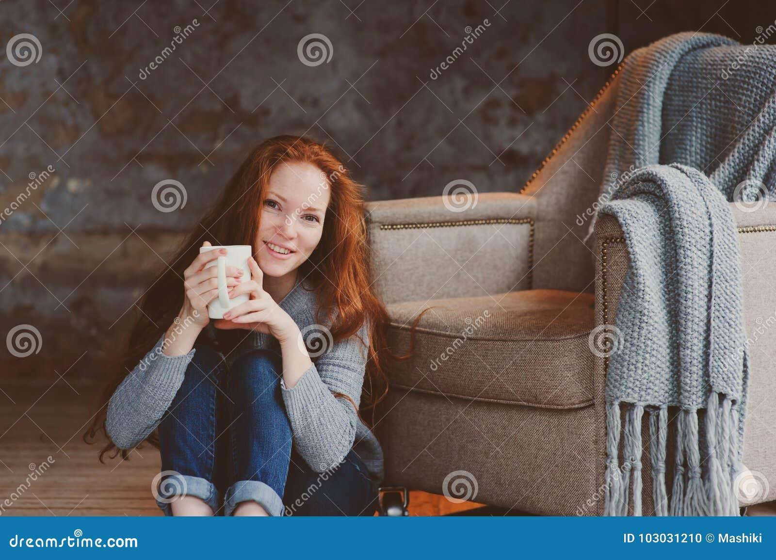 在家喝热的咖啡或茶的愉快的年轻readhead妇女 镇静和舒适周末在冬天