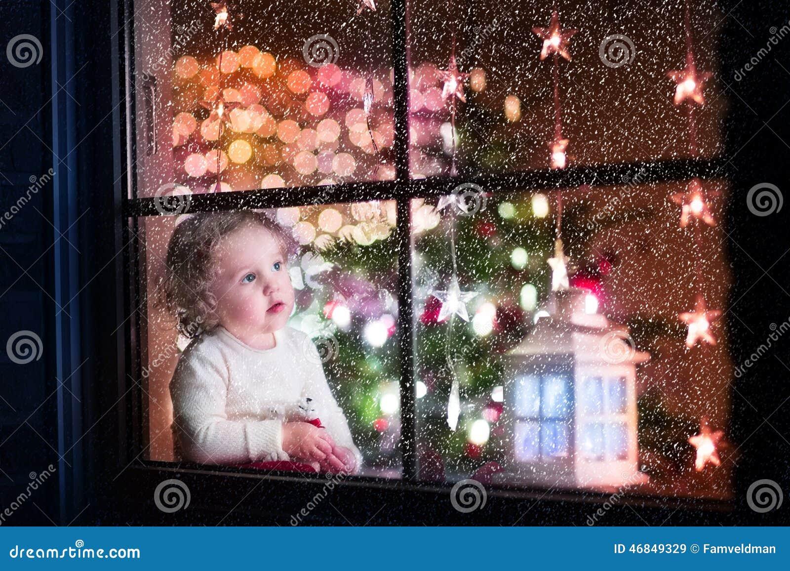在家坐与玩具熊的逗人喜爱的卷曲小孩女孩在圣诞节时间,准备庆祝Xmas伊芙